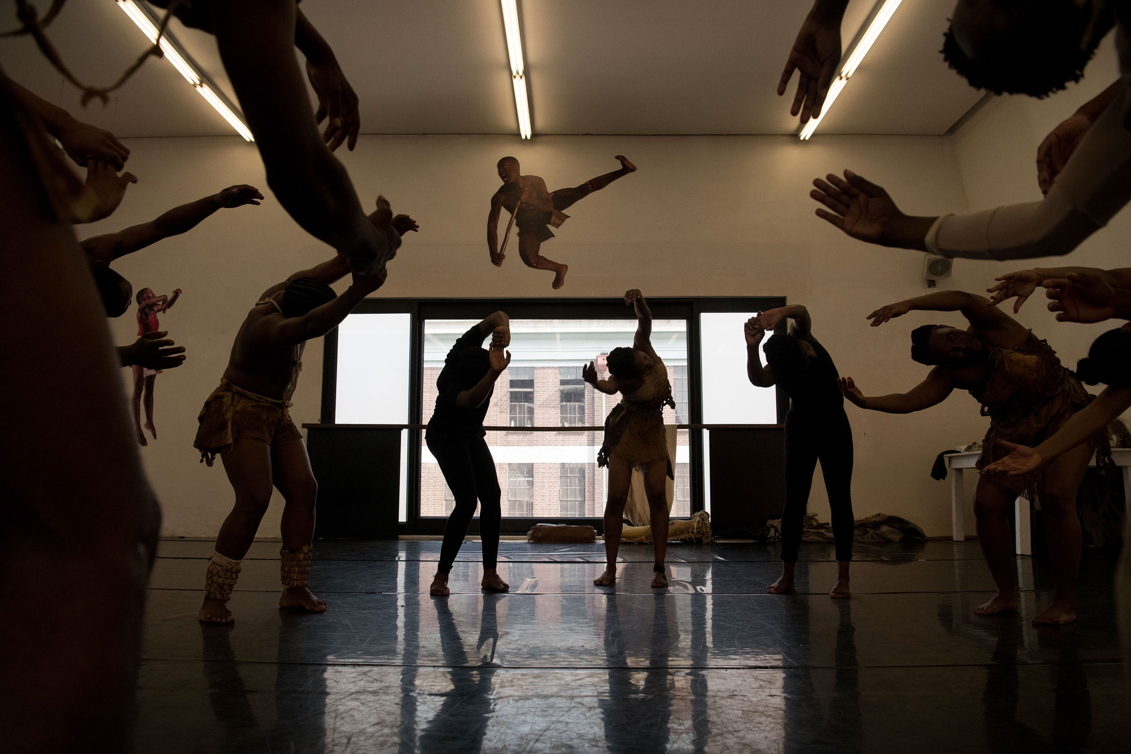 18 September 2019: In silhouette, the Moving into Dance dancers go through the routine of Sylvia Glasser's iconic work, premised on images found in San rock art.