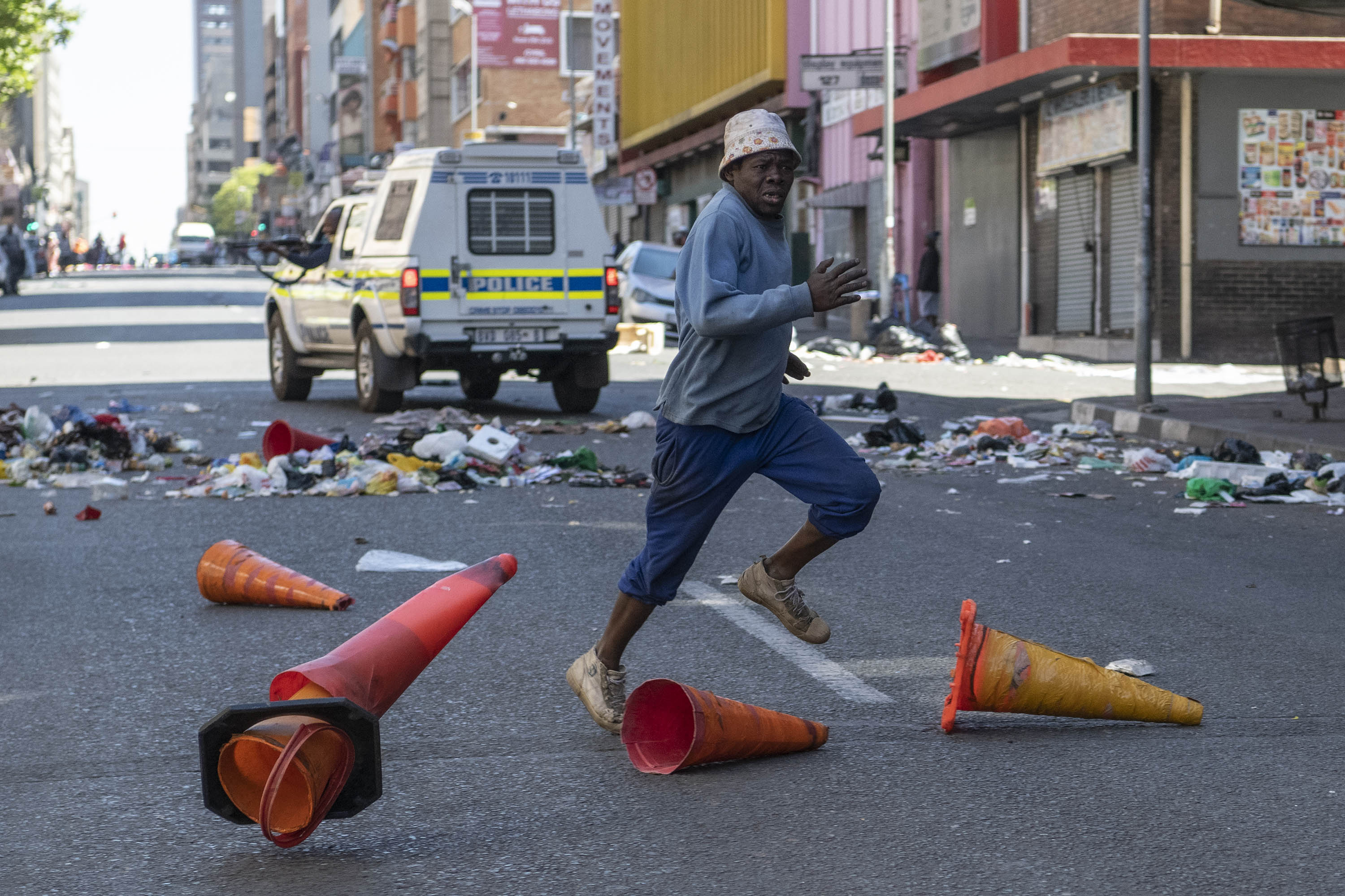 2 September 2019: A man running for cover as police officers attempt to disperse the group looting businesses in Joburg's central business district.