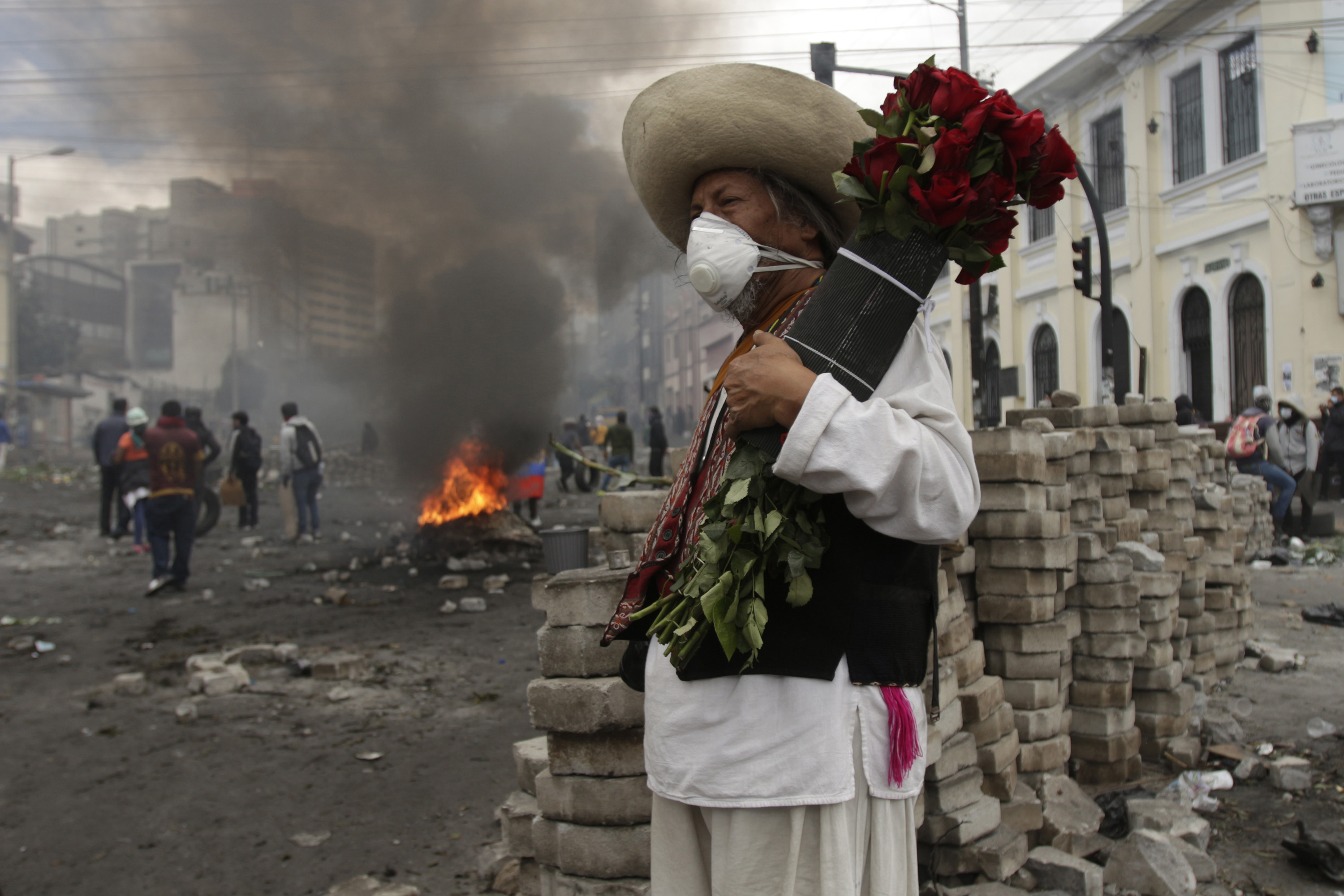 12 October 2019: A demonstrator holds a bouquet of roses in front of a burning barricade during the indigenous protests against the economic measures taken by President Lenín Moreno in Quito, Ecuador. (Photograph by Ricardo Landera/Agencia Press South/Getty Images)