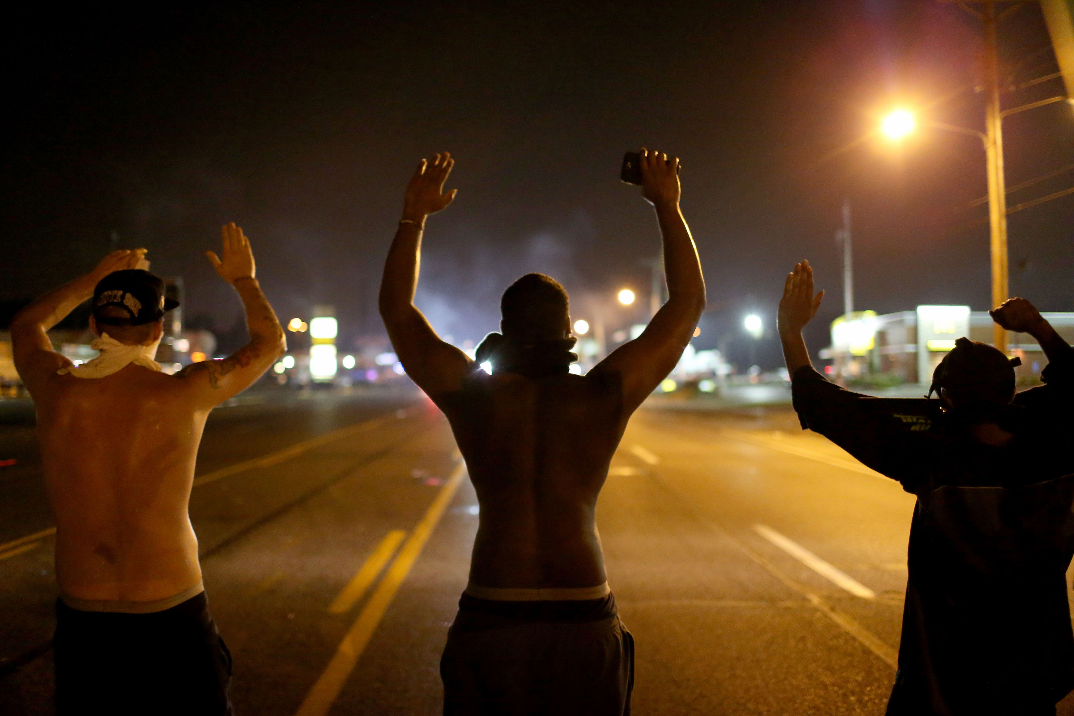 "17 August 2014: Demonstrators raise their arms and chant, ""Hands up, Don't Shoot"", while police clear them from the street as they protest the shooting death of Michael Brown on 9 August 2014 in Ferguson, Missouri. (Photograph by Joe Raedle/Getty Images)"