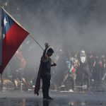 21 October 2019: A demonstrator in Santiago waving a Chilean flag during protests against President Sebastián Piñera, sparked by his announcement of a hike in peak subway fares. (Photograph by Marcelo Hernandez/Getty Images)