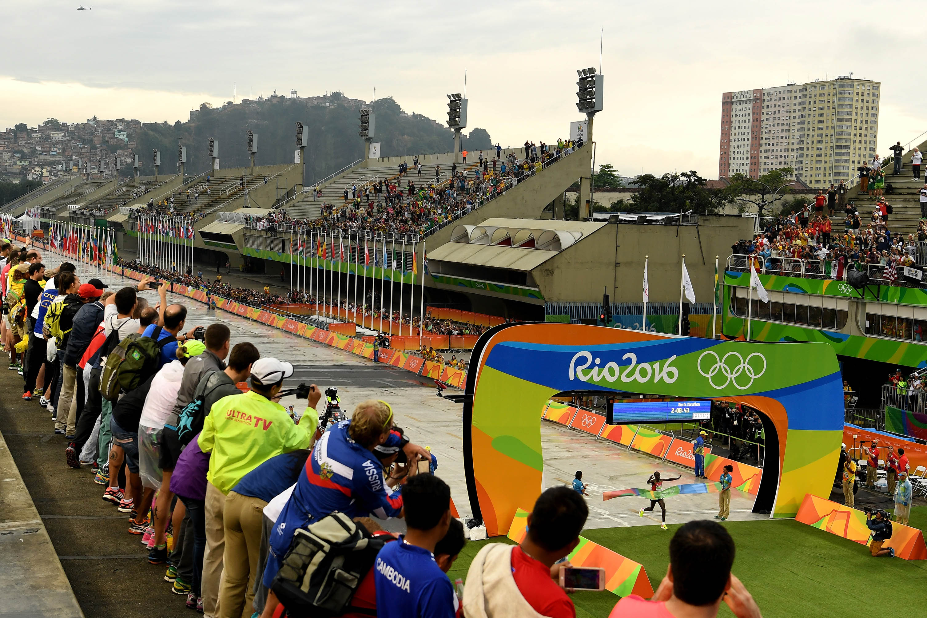 21 August 2016: Spectators watching as Kenyan runner Eliud Kipchoge crosses the line to win gold in the men's marathon at the 2016 Olympic Games at Sambódromo in Rio de Janeiro, Brazil. (Photograph by Quinn Rooney/Getty Images)