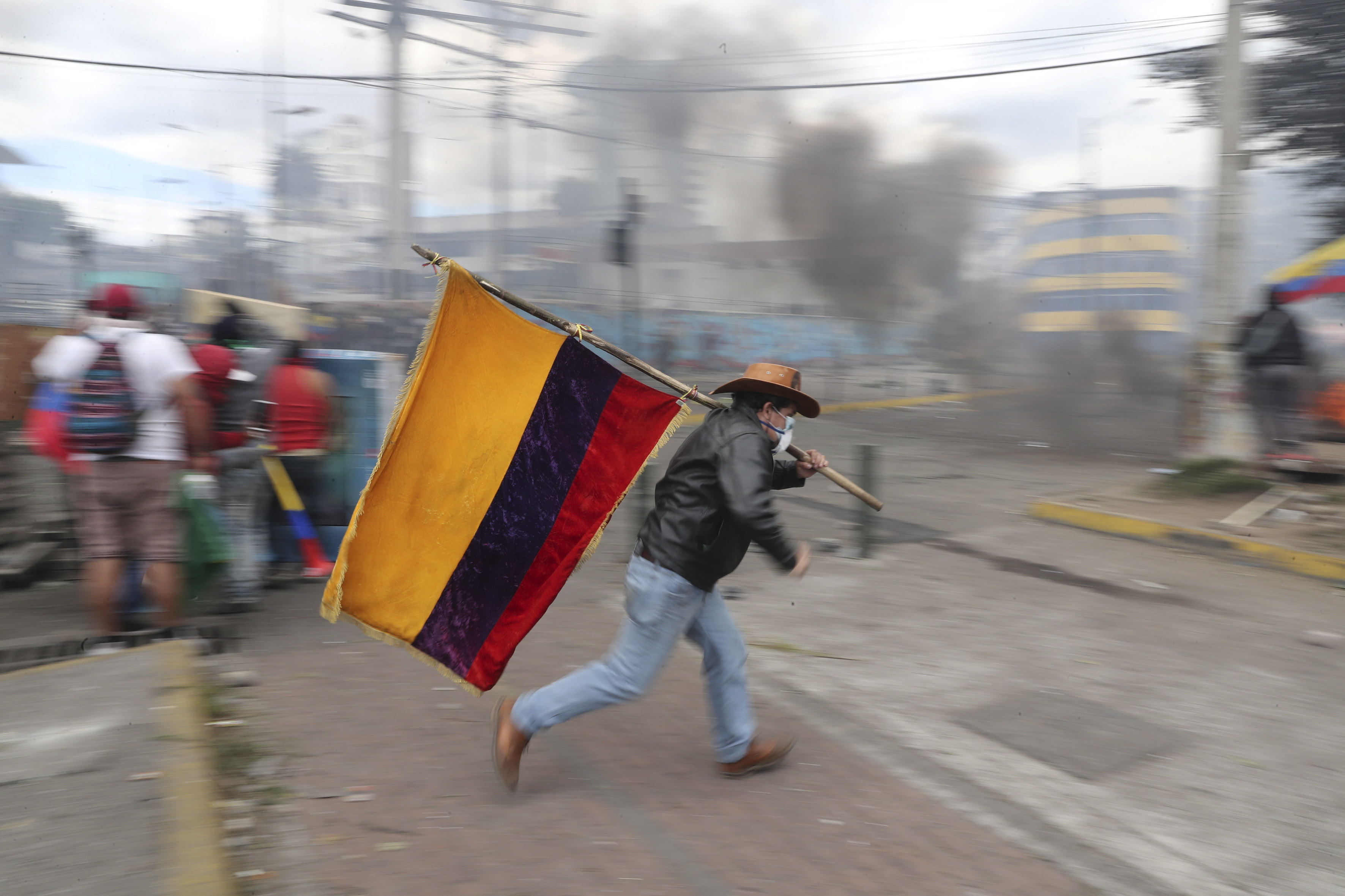 12 October 2019: A demonstrator running while holding an Ecuadorian flag in Quito, Ecuador, during a protest against President Lenín Moreno's austerity measures. (Photographs by Reuters/Ivan Alvarado)