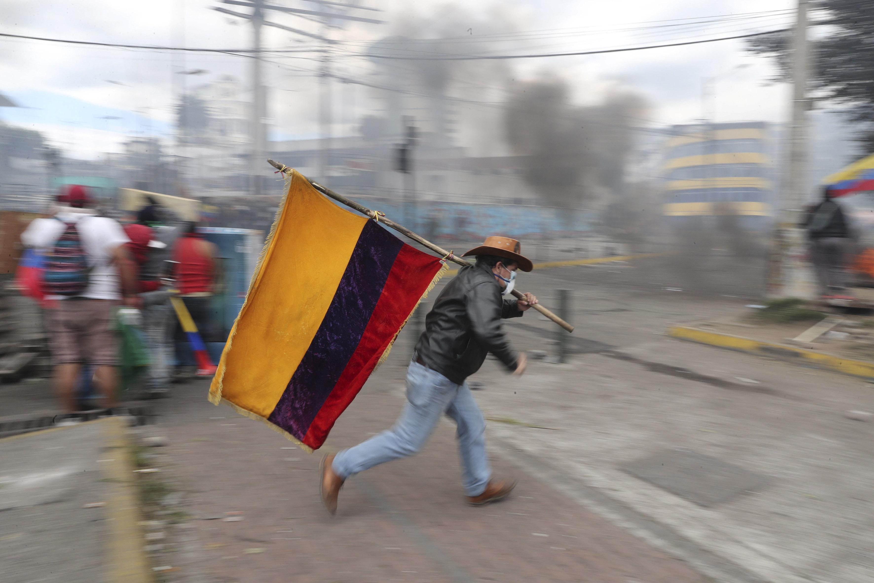 12 October 2019: A demonstrator running while holding an Ecuadorian flag in Quito, Ecuador, during a protest against President Lenín Moreno's austerity measures. (Photographs by Reuters/Ivan Alvarado)