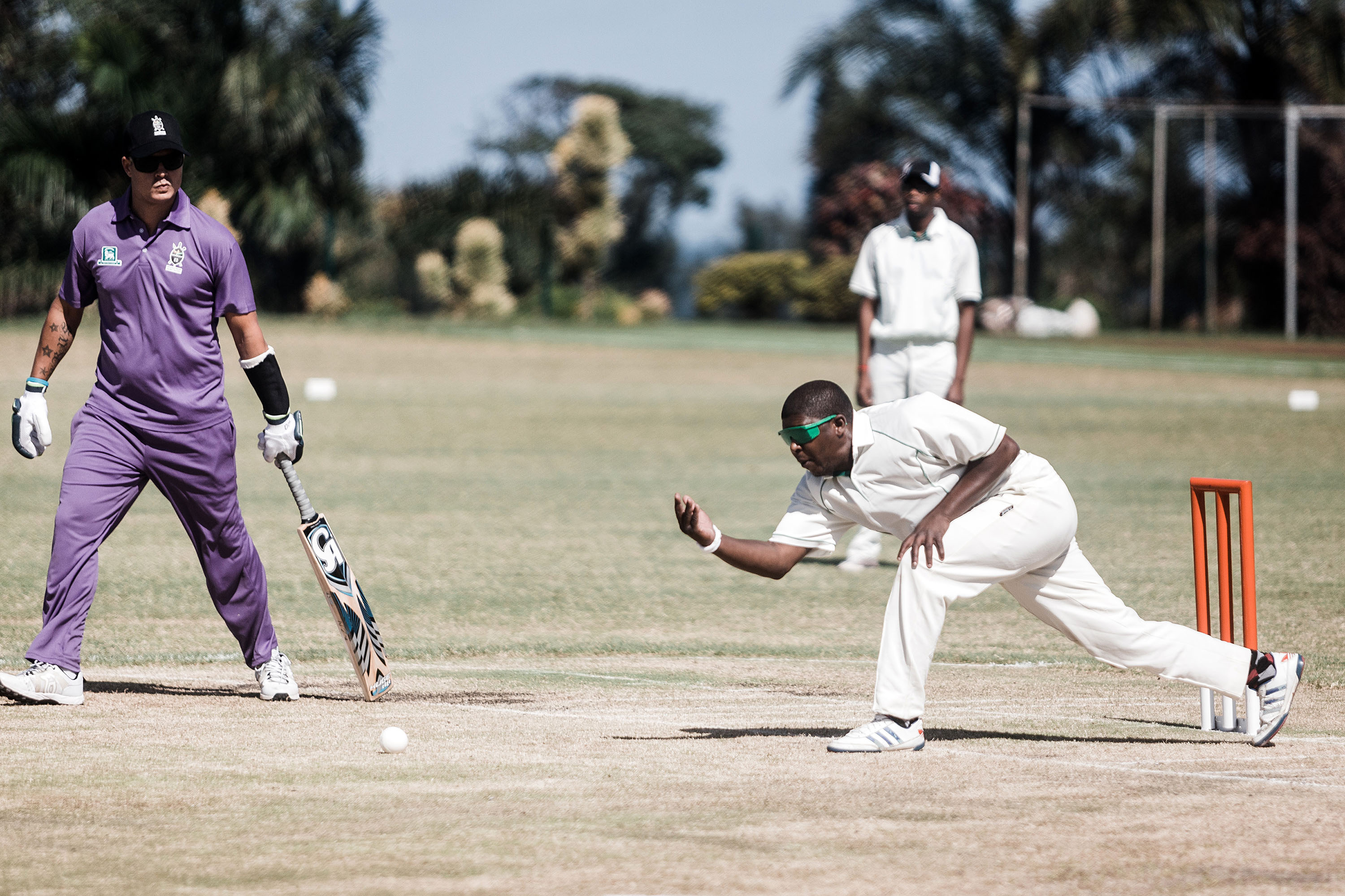 25 September 2019: A player from the Free State, in white, bowls against Kwazulu-Natal in purple. Blind and partially sighted cricketers rely on commentary from fellow players to gauge the path of the ball.