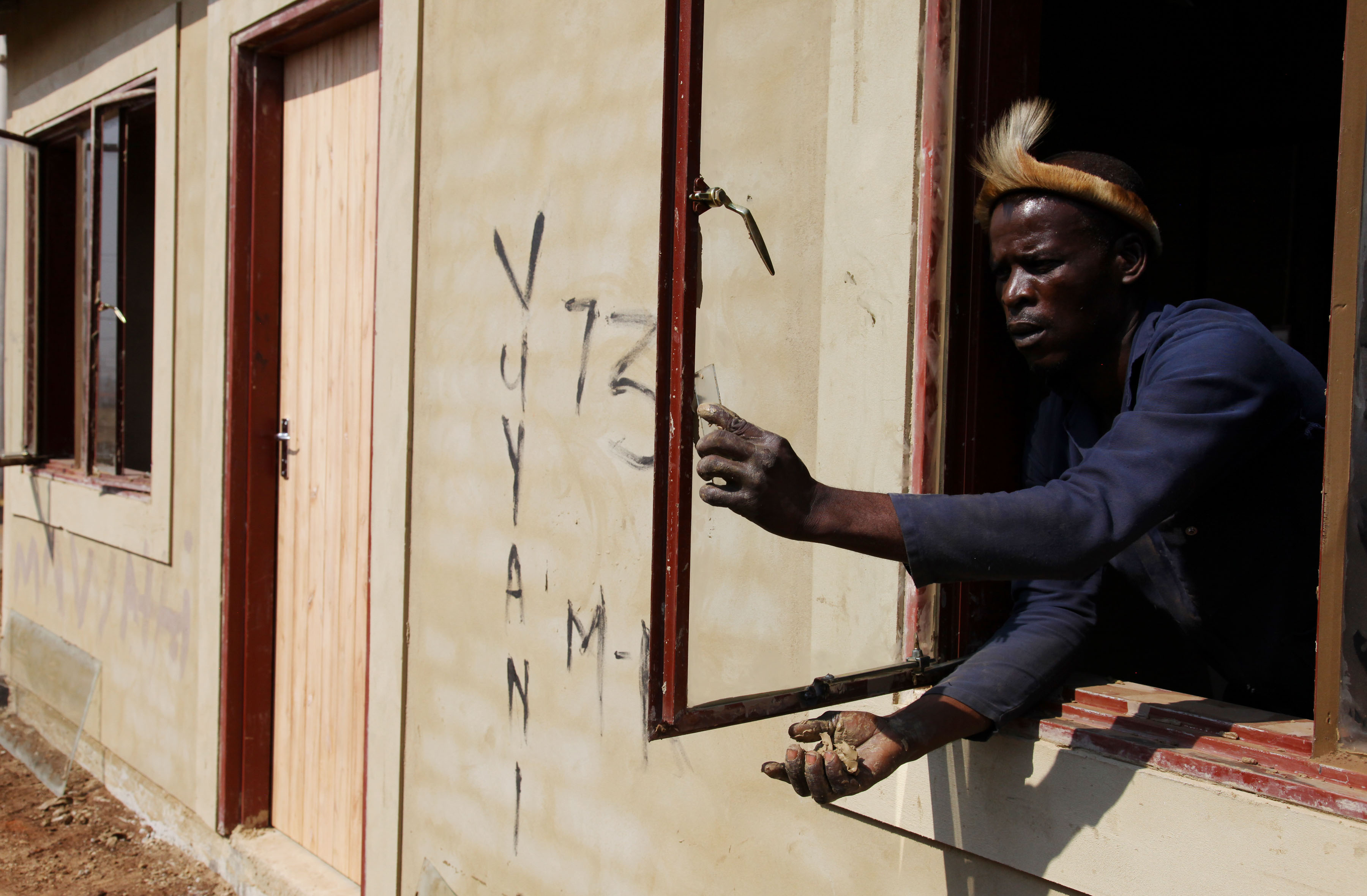 7Oct_MKVets_BB-5 08 August 2019: A subcontractor, Sipho Ntimba,  installs a new window during building on an MK veteran's RDP house.