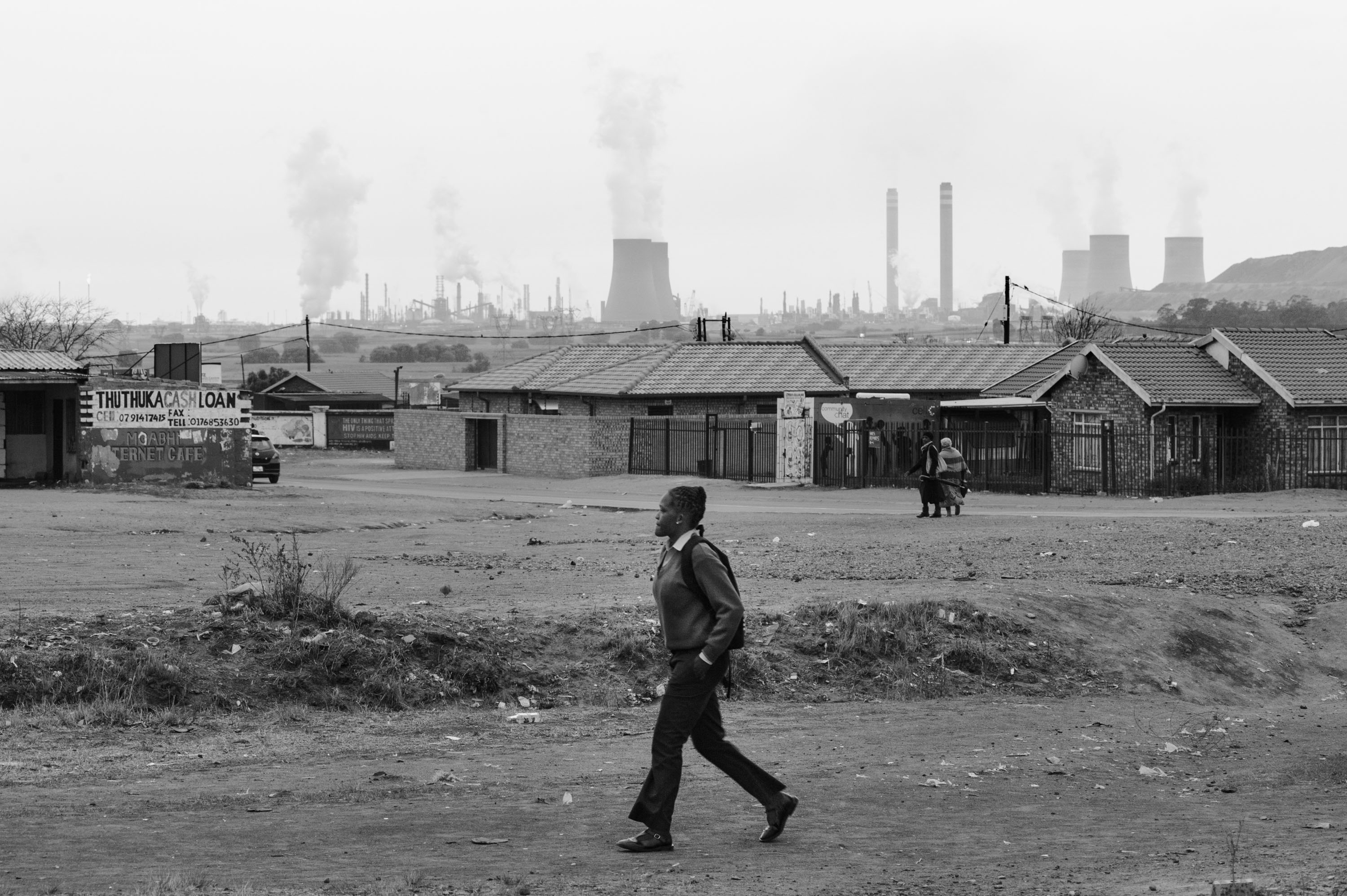 A student walks through eMbalenhle township near Secunda with the Sasol Synfuels Plant in the background. Many people in eMbalenhle suffer from tuberculosis, asthma and other respiratory diseases. eMbalenhle, Mpumalanga.