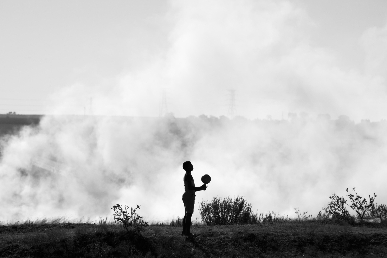 Child playing with ball near veld fire. Phola, Mpumalanga.