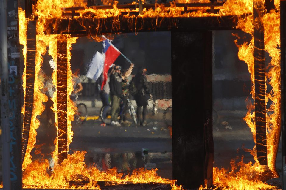 21 October 2019: A demonstrator waving a Chilean flag during a protest against President Sebastian Piñera's subway fare hike in Santiago, Chile. Protests in a number of cities developed into looting and arson. (Photograph by Marcelo Hernandez/Getty Images)