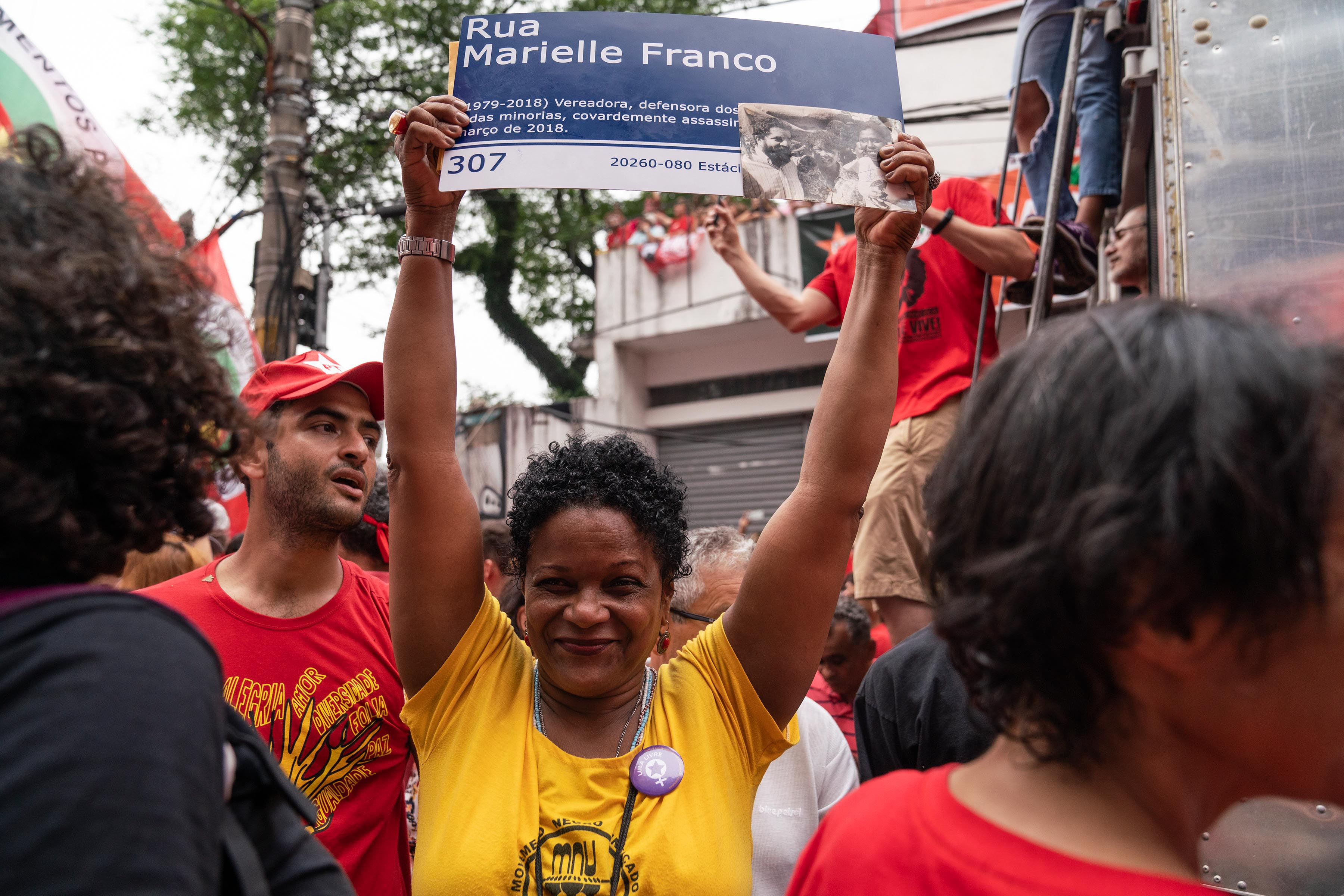 9 November 2019: A woman holds up a poster with the name of the human rights defender, Marielle Franco, who was murdered in Rio de Janeiro last year.