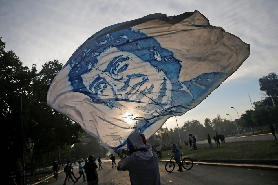 22 October 2019: A demonstrator waves a flag portraying the celebrated Chilean singer-songwriter Víctor Jara during a protest in the capital, Santiago, against Chile's state economic model. (Photograph by Reuters/Edgard Garrido)