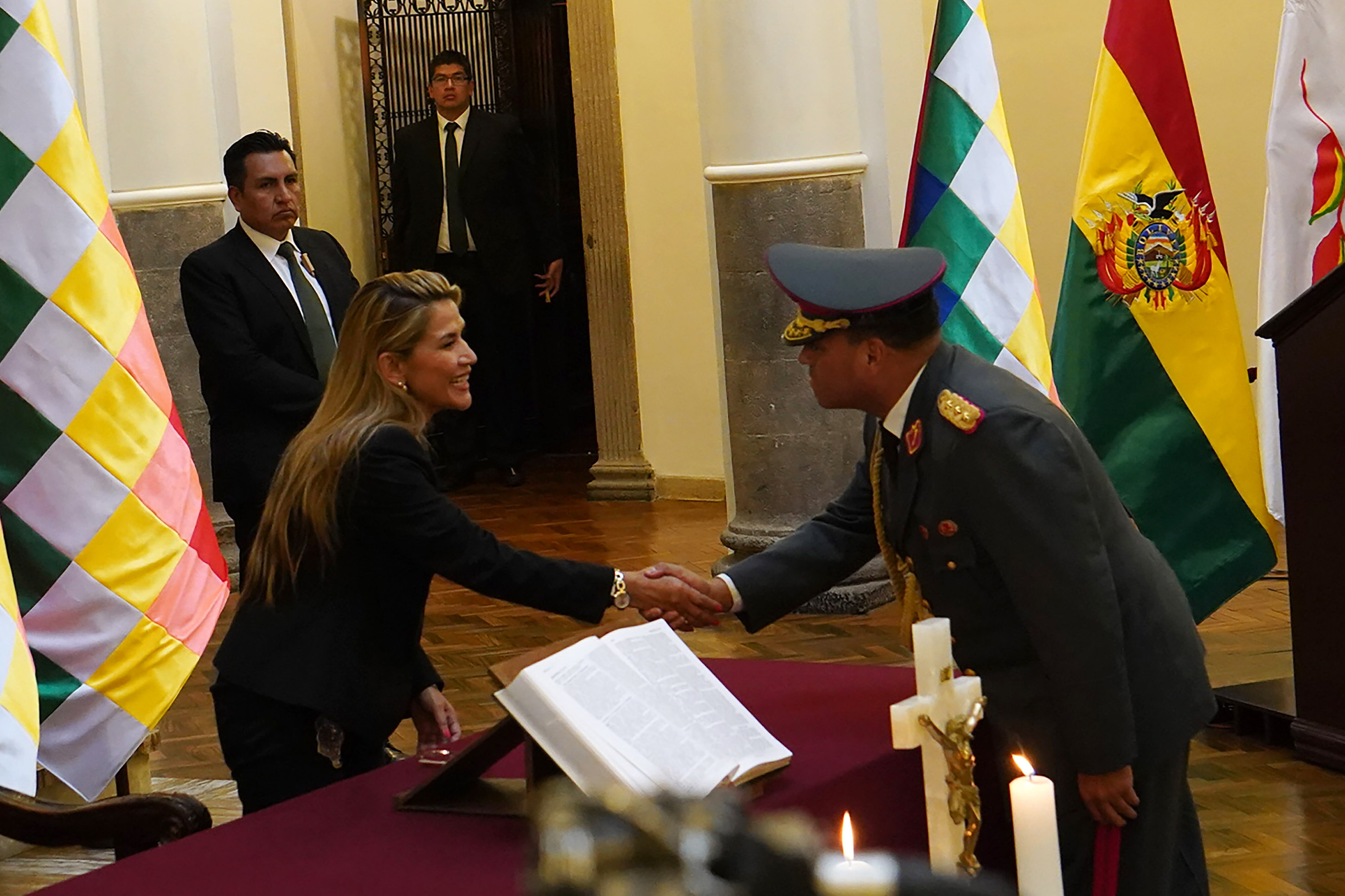 13 November 2019: Interim Bolivian President Jeanine Áñez shakes hands with new commandant in chief of the armed forces General Sergio Orellana Centellas at the presidential palace in La Paz, Bolivia. (Photograph by Javier Mamani/Getty Images)