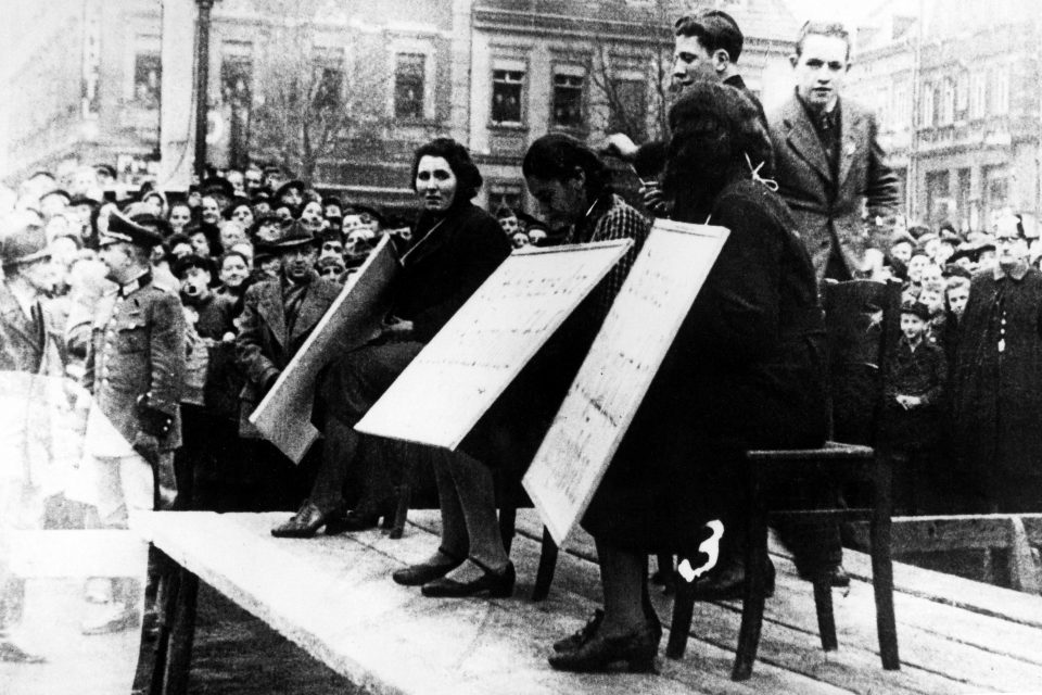 November 1938: Jewish women in Linz, Austria, are humiliated in public by having cardboard signs strung around their necks reading, 'I have been excluded from the national community (Volksgemeinschaft)'. (Photograph by Galerie Bilderwelt/Getty Images)