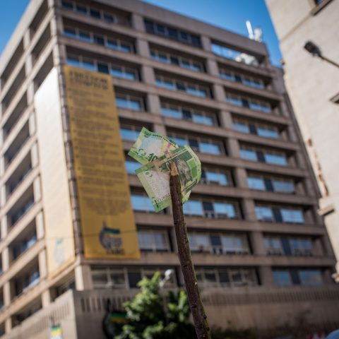 25 April 2018: A protester holds up two R10 notes on a stick in front of ANC headquarters Luthuli House in Johannesburg, in opposition to the proposed minimum wage of R20 an hour. This became the legal rate on 1 January 2019. (Photograph by Daylin Paul)