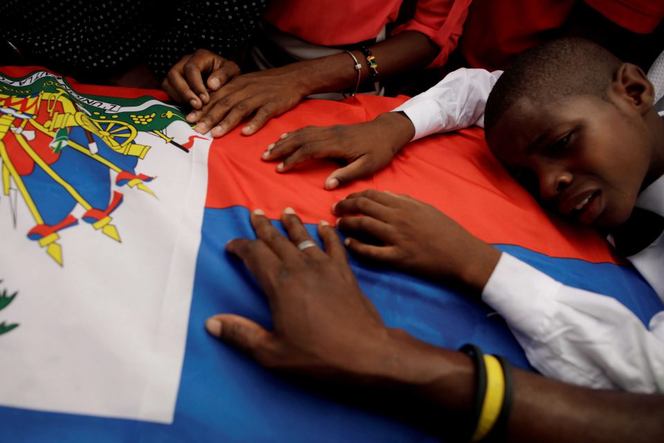 16 October 2019: A boy cries on the Haitian flag draping a coffin during a funeral for two men organised by the Popular and Democratic Sector in Port-au-Prince, Haiti. (Photograph by Reuters/Andres Martinez Casares)