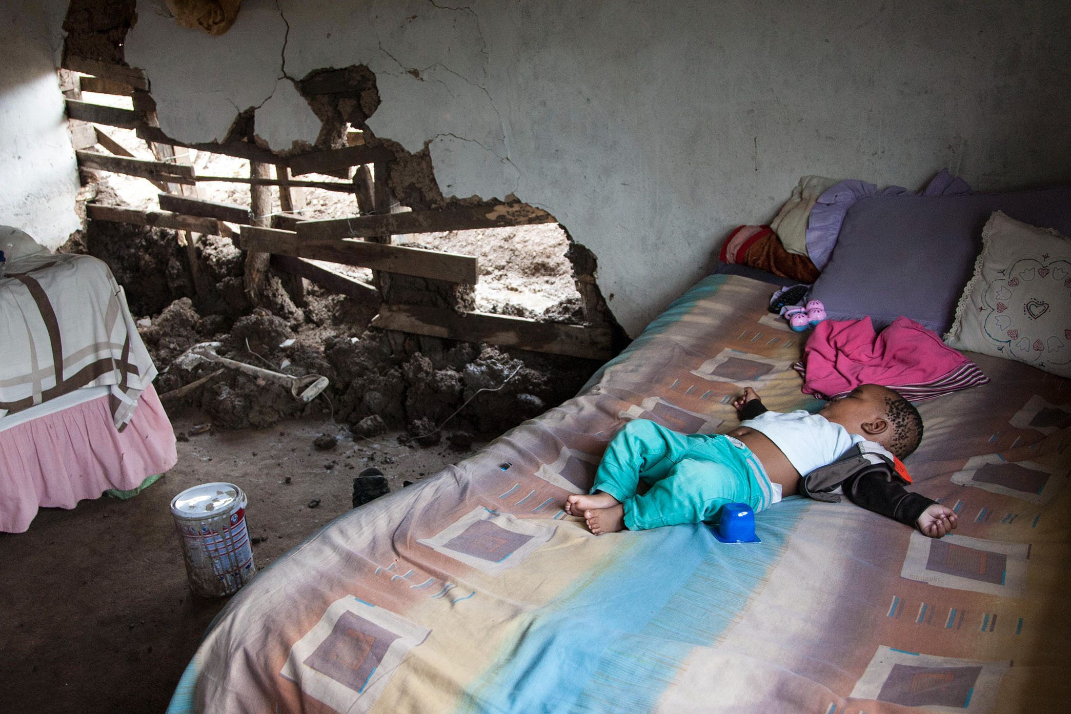 16 November 2019: Athenkosi Maphenduka sleeps in the room he shares with his grandmother at their home in Tommy Property shack settlement in Mhlasini, KwaZulu-Natal. Heavy rain washed away the lower wall of their mud house.