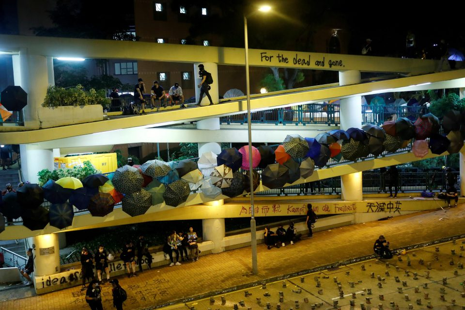 13 November 2019: Umbrellas stuck in the handrails of a footbridge leading to the occupied campus of the Hong Kong Baptist University. (Photograph by Reuters/Thomas Peter)