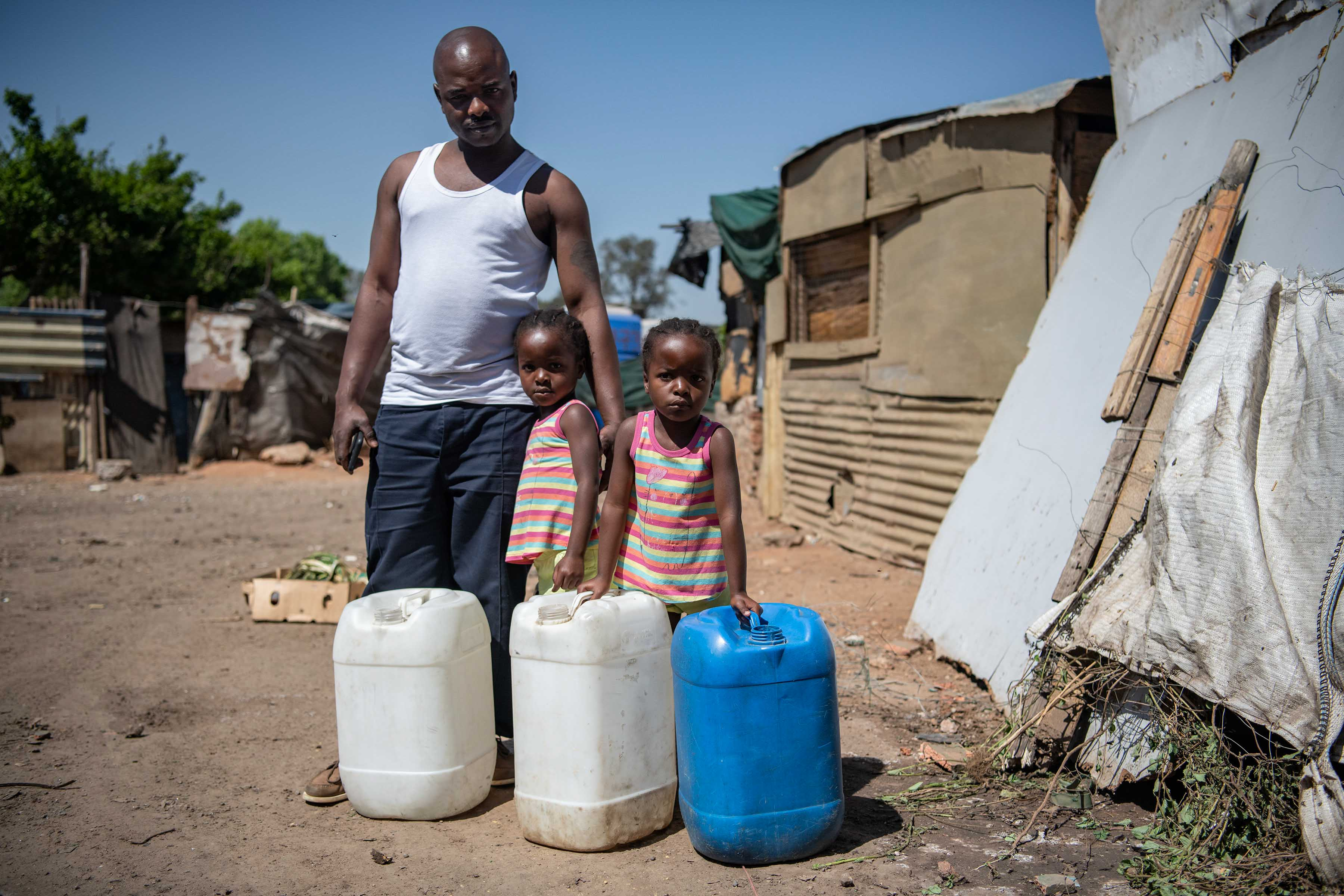1 October 2019: Shandu Mamuremi and his twin daughters going to fetch water in Makause, where there are few communal taps.
