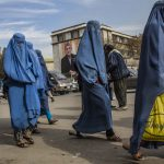 7 November 2019: Afghan women walk past a poster of President Hamid Karzai displayed on the side of the City Hall in Kabul, Afghanistan. (Photograph by Daniel Berehulak/Getty Images)