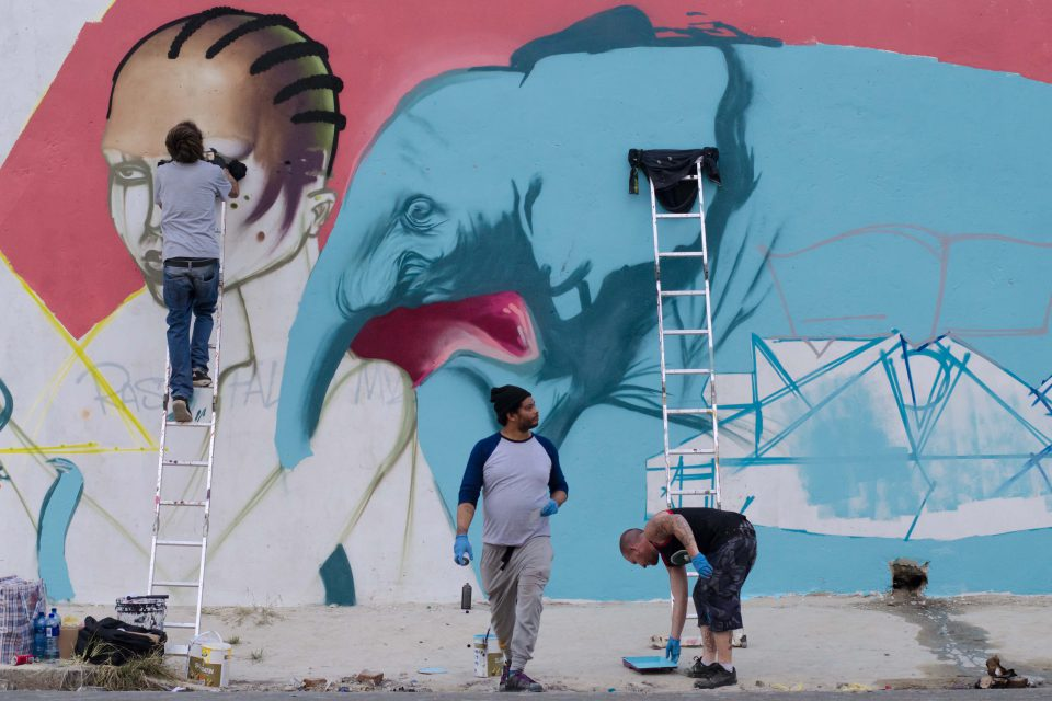 26 July 2016: From left, Rasty, Falko and Myza working on a collaborative mural in Jeppestown, Johannesburg. (Photograph by Tseliso Monaheng)