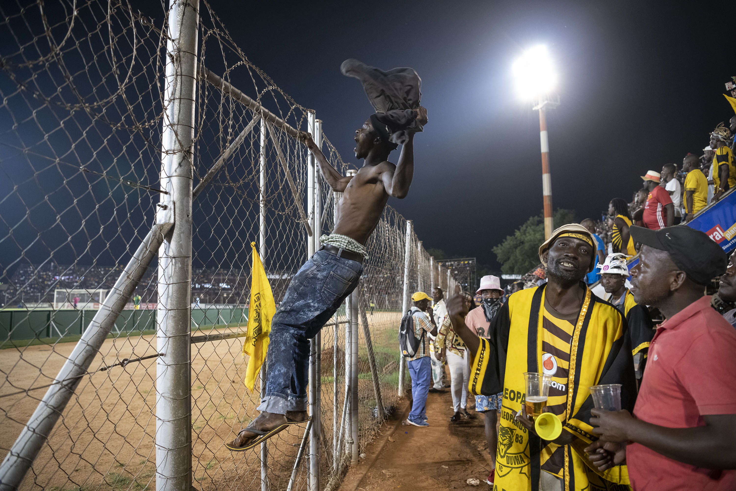 30 November 2019: A Black Leopards fan climbs the security fence in front of the Zamalek stand to berate the referee.