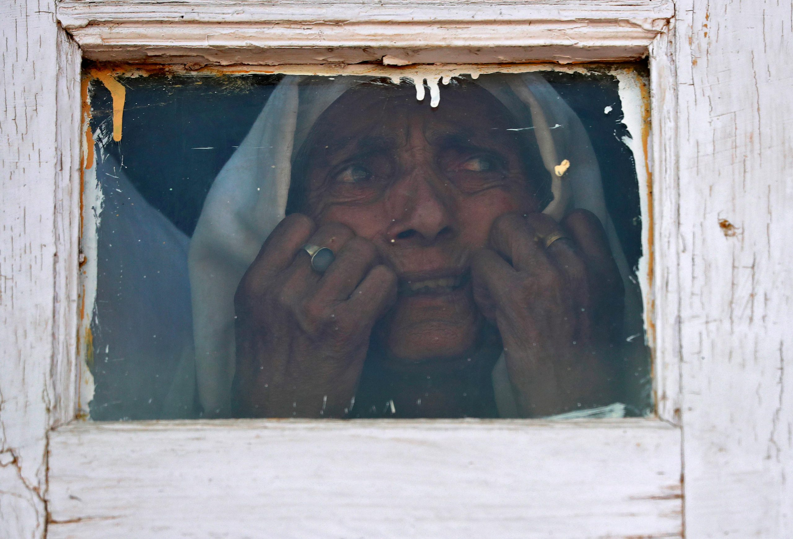 13 September 2019: A Kashmiri woman in Srinagar looks out from a mosque window at a protest about the Indian government scrapping the special constitutional status of Kashmir.