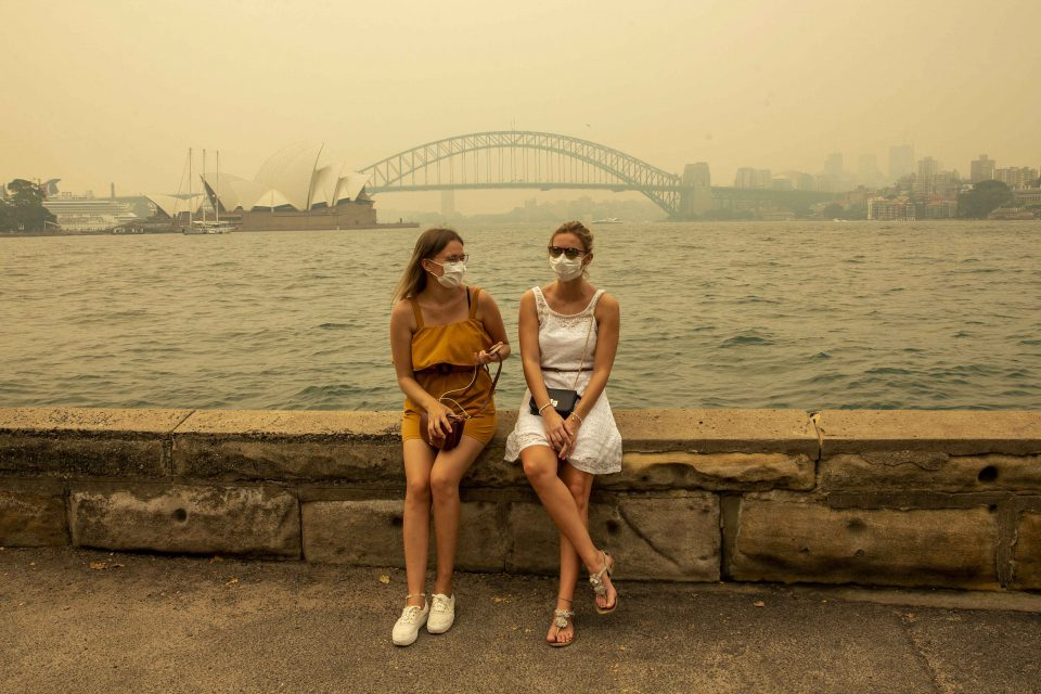 19 December 2019: From left: Tourists Julia Wasmiller and Jessica Pryor wear face masks while visiting Mrs Macquarie's Chair in Sydney, Australia, to avoid inhaling heavy smoke from the almost 100 bushfires burning across the state. (Photograph by Jenny Evans/Getty Images)