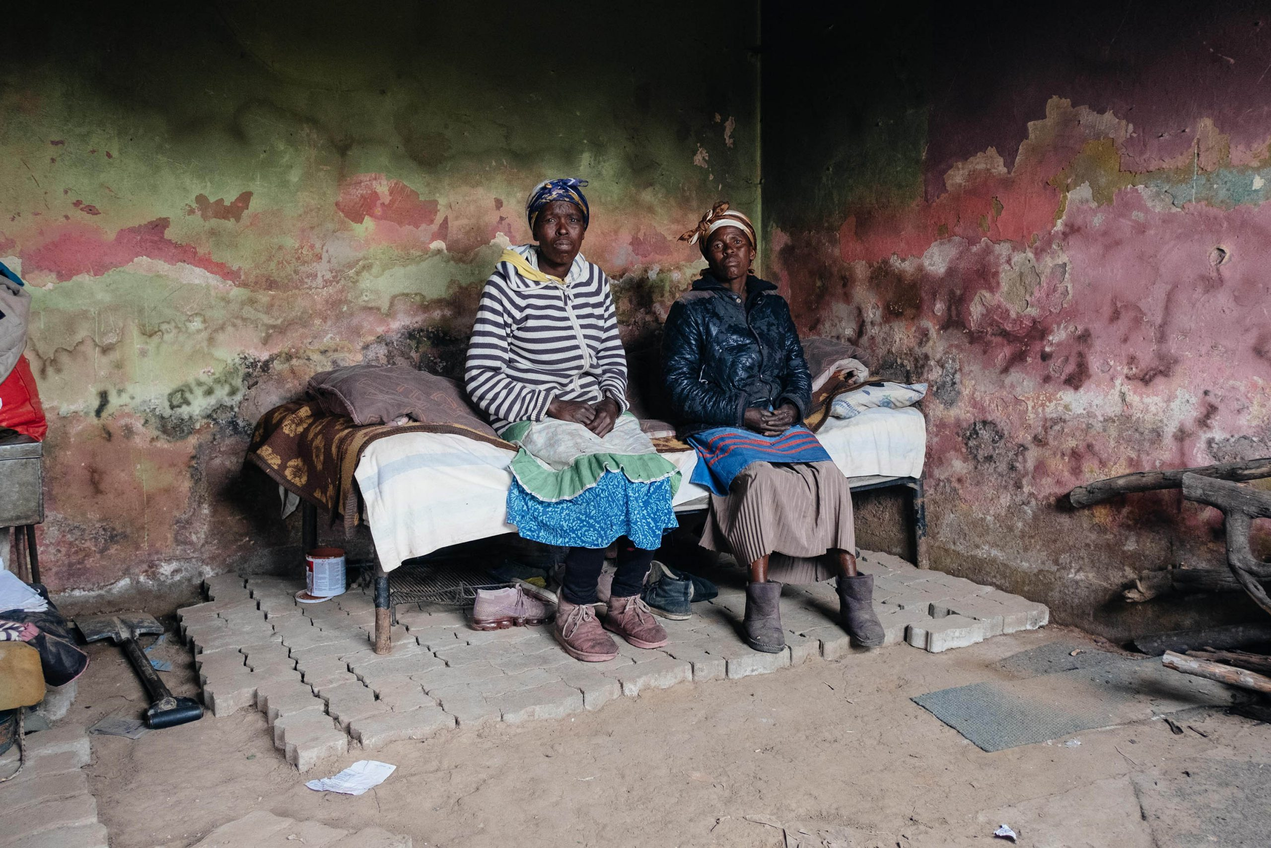 10 December 2019: From left, Lindiwe Mbundana, 54, and Nonkoliso Mbundana, 51, in the room they share in a house in Old Location. The house has no electricity or running water.