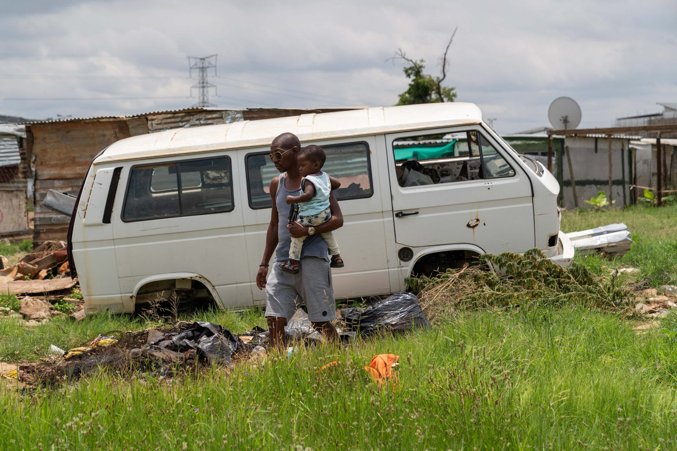 21 January 2020: Mandla Mahlangu, a Seven Seven leader, walks past a wrecked Kombi and other flood damage.