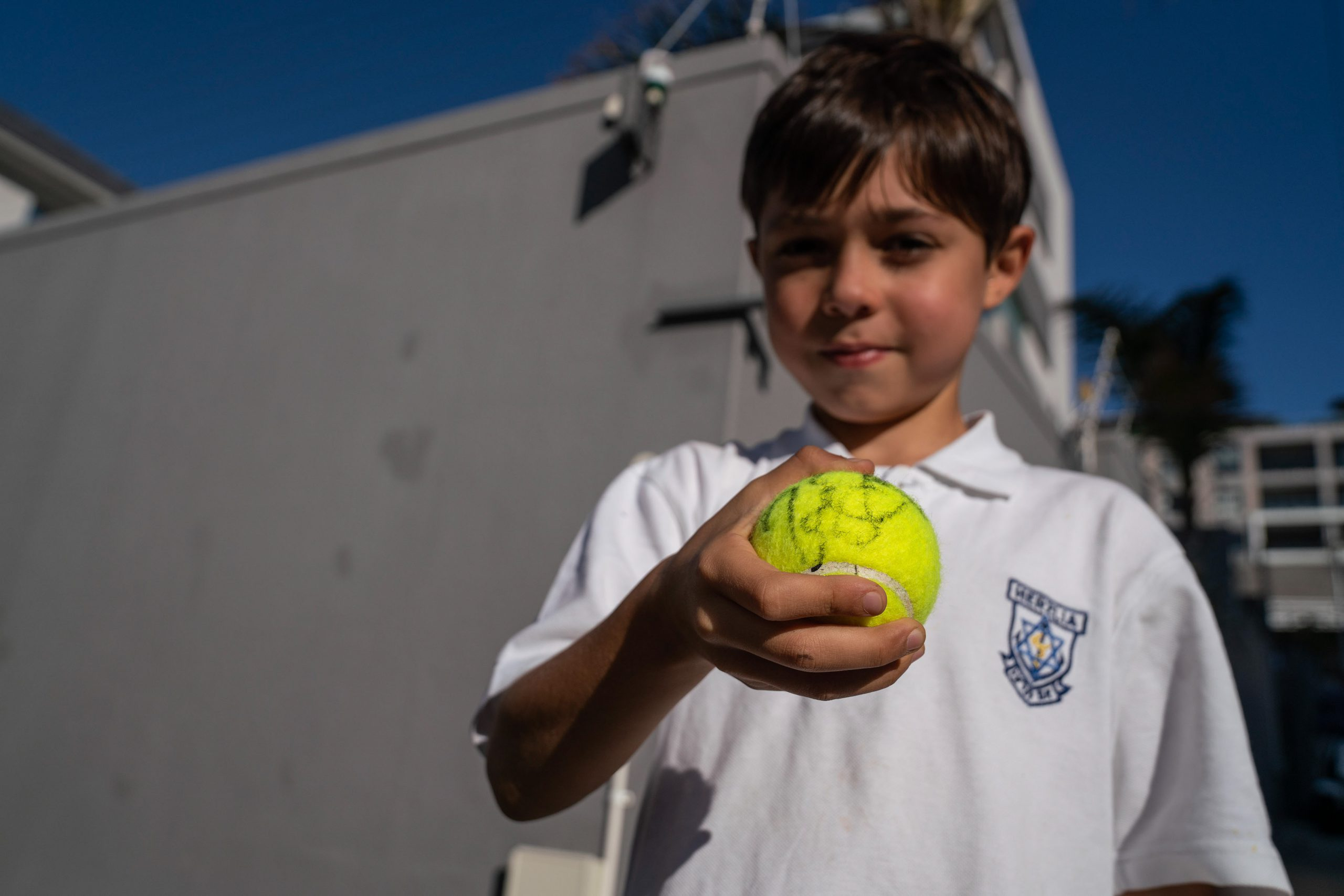 6 February 2020: Tennis fan Jonah Khan shows off a ball signed by Roger Federer after the legend visited the Anthony Harris Tennis Academy in Sea Point.