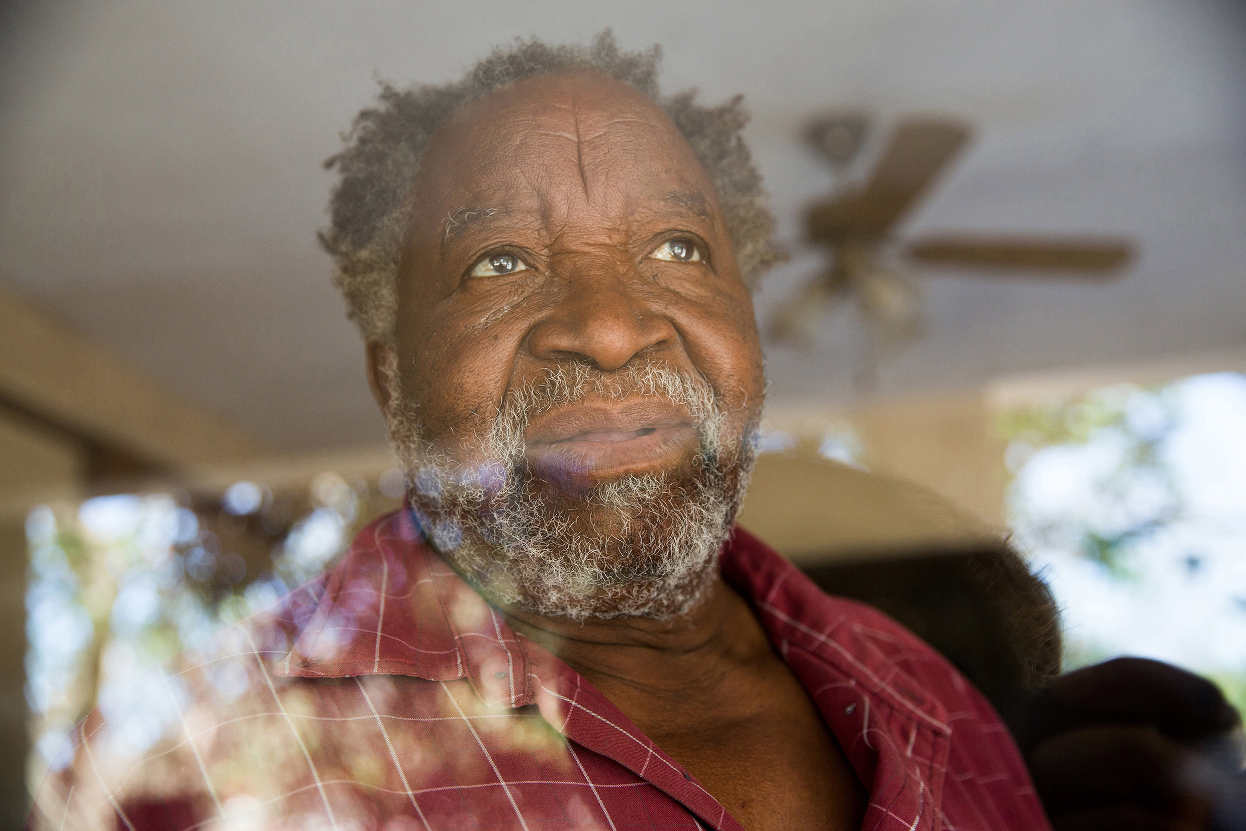 25 November 2018: Khotiza Ngubane looks through the window of his home at the lemon tree Clare Stewart planted shortly before her death.