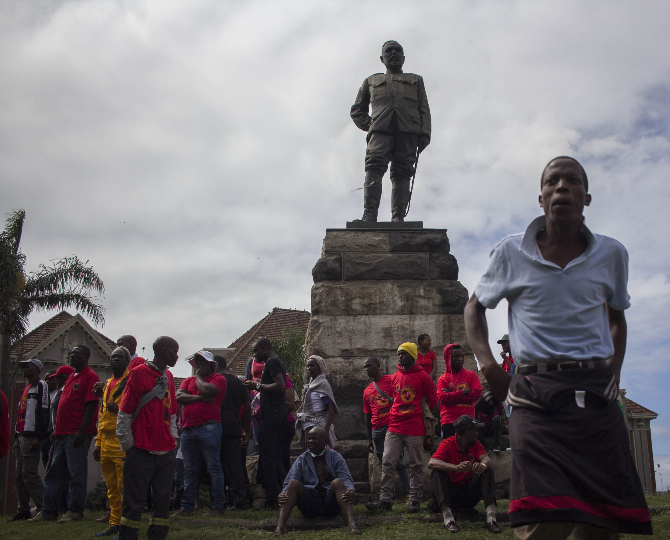 24 February 2020: A statue of Louis Botha, first prime minister of the Union of South Africa, towers over supporters of Abahlali baseMjondolo as they gather before the march.