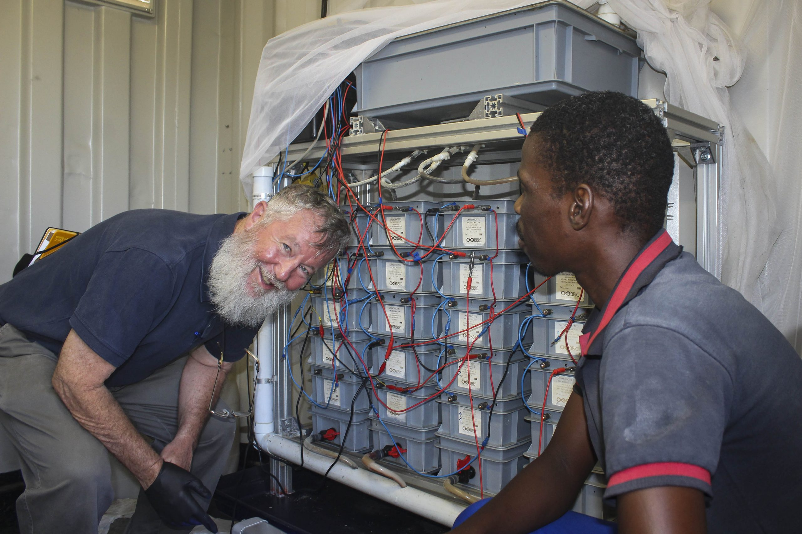 "24 January 2020: Chris Buckley and community liaison officer Nelson Khumalo inspect the business end of the ""uricity"" prototype power plant, which collects urine from a communal ablution block at a Durban shack settlement. (Photographs by Tony Carnie)"