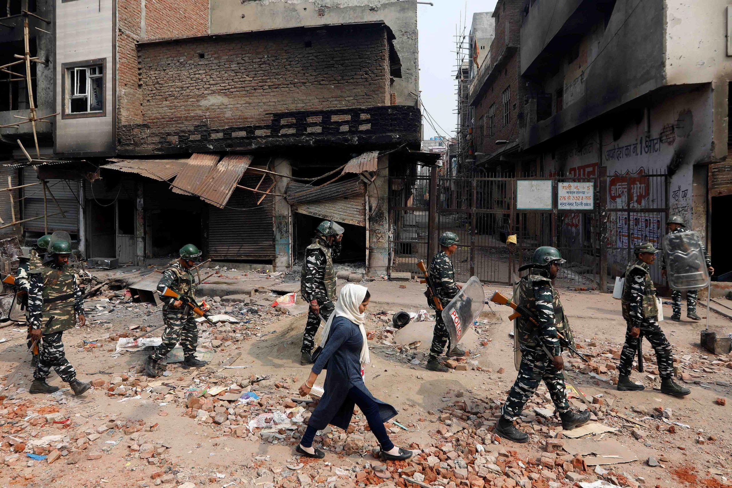 26 February 2020: A woman walks past security forces patrolling in a riot-affected area of New Delhi. Clashes broke out between those supporting and opposing the controversial new Citizenship Amendment Act as some fear it will be used to strip India's Muslim population of their citizenship. (Photograph by Reuters/Adnan Abidi)