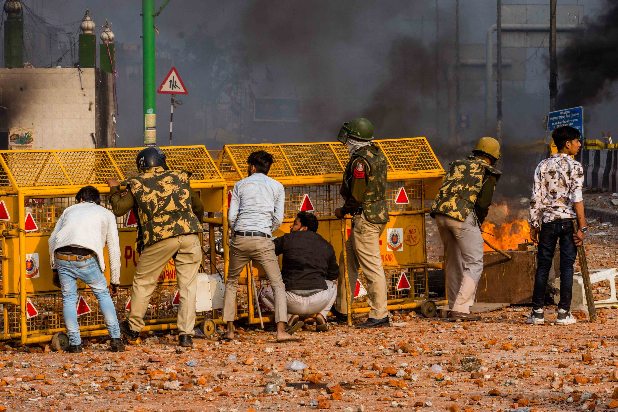 24 February 2020: Indian police officers and supporters of a new citizenship law seek shelter as protesters throw bricks and stones at them during clashes over the Citizenship Amendment Act in New Delhi. The civilian on the far right appears to be the same man on the right of the group attacking Mohammad Zubai (see top photograph), suggesting that they may have been working with the police. (Photograph by Yawar Nazir/Getty Images)