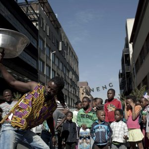 26 May 2012: A street artist performs a dance as children look on in Maboneng, a gentrified district in downtown Johannesburg. (Photograph by Per-Anders Pettersson/Getty)