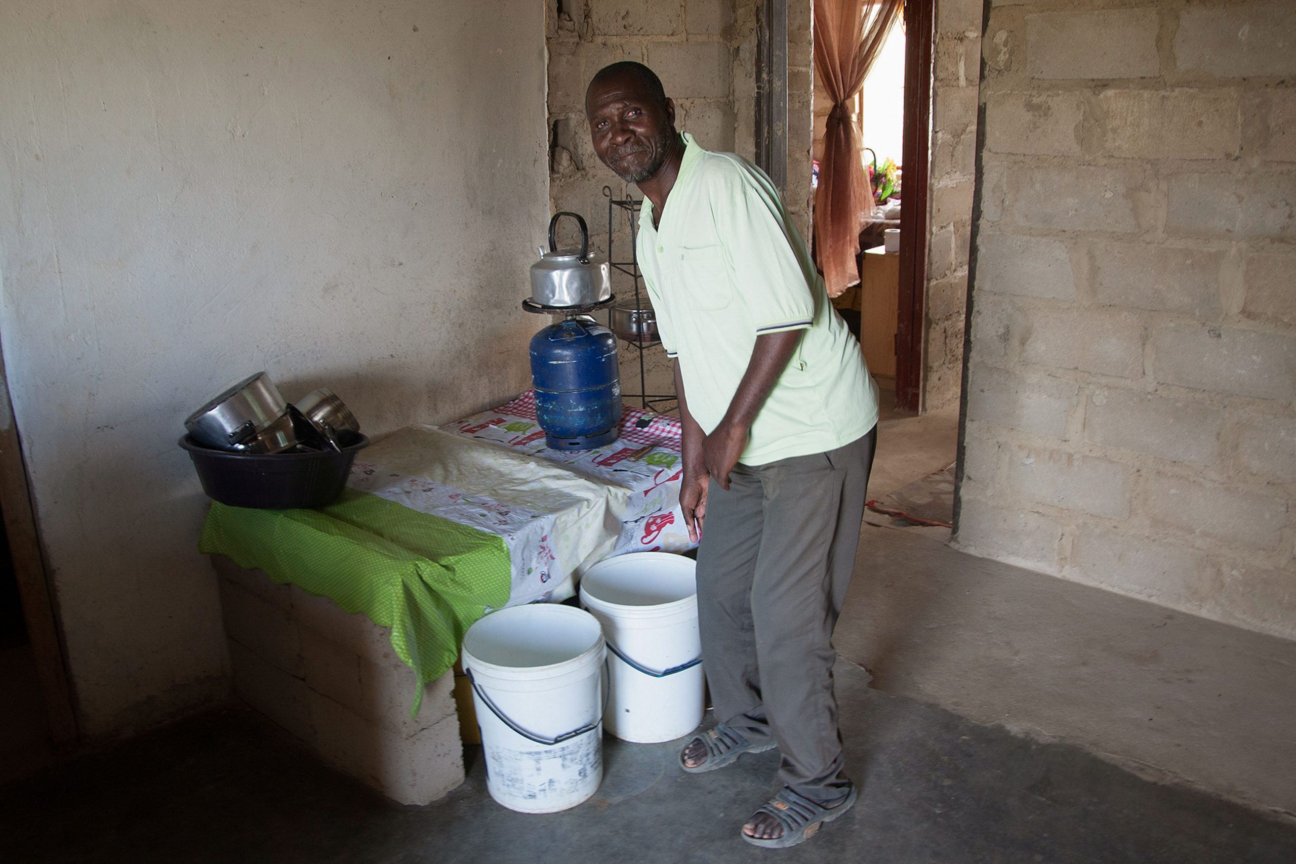 13 March 2020: Kgutsana Heisi Molefe uses buckets to carry water to his home in Jimane outside Vryheid.