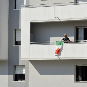 19 March 2020: A woman drapes the Italian flag from her balcony in Trento after the government took the unprecedented step of a nationwide lockdown, only allowing people to go to work or health centres. (Photograph by Alessio Coser/ Getty Images)