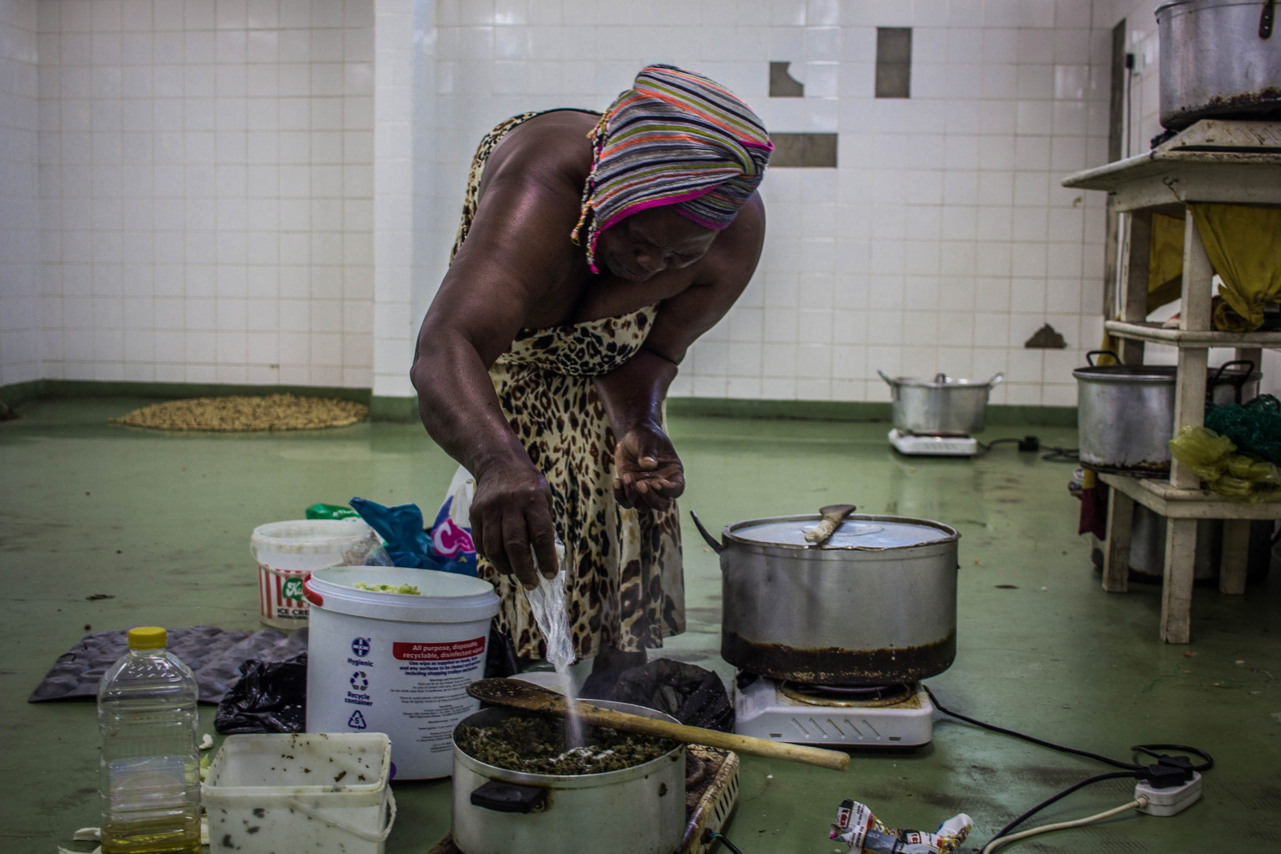 13 February 2020: Thandiwe Khathi adds salt to her food. One of the oldest women at the hostel, she wakes up at around 5am and begins to prepare food for her customers.