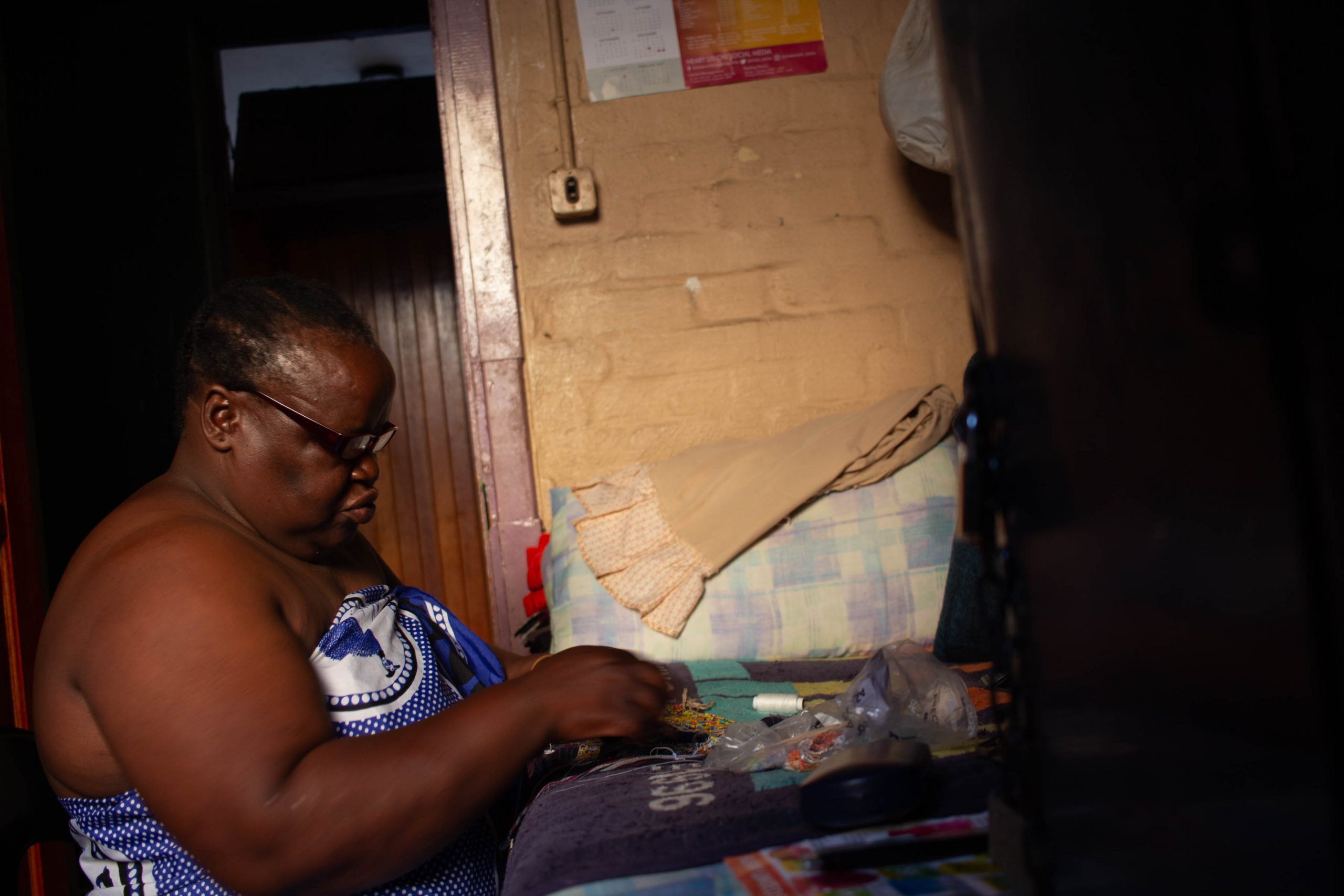 13 February 2020: Busi Msomi is a beader. She works in her room, using coloured beads to create her designs by the light from her window.
