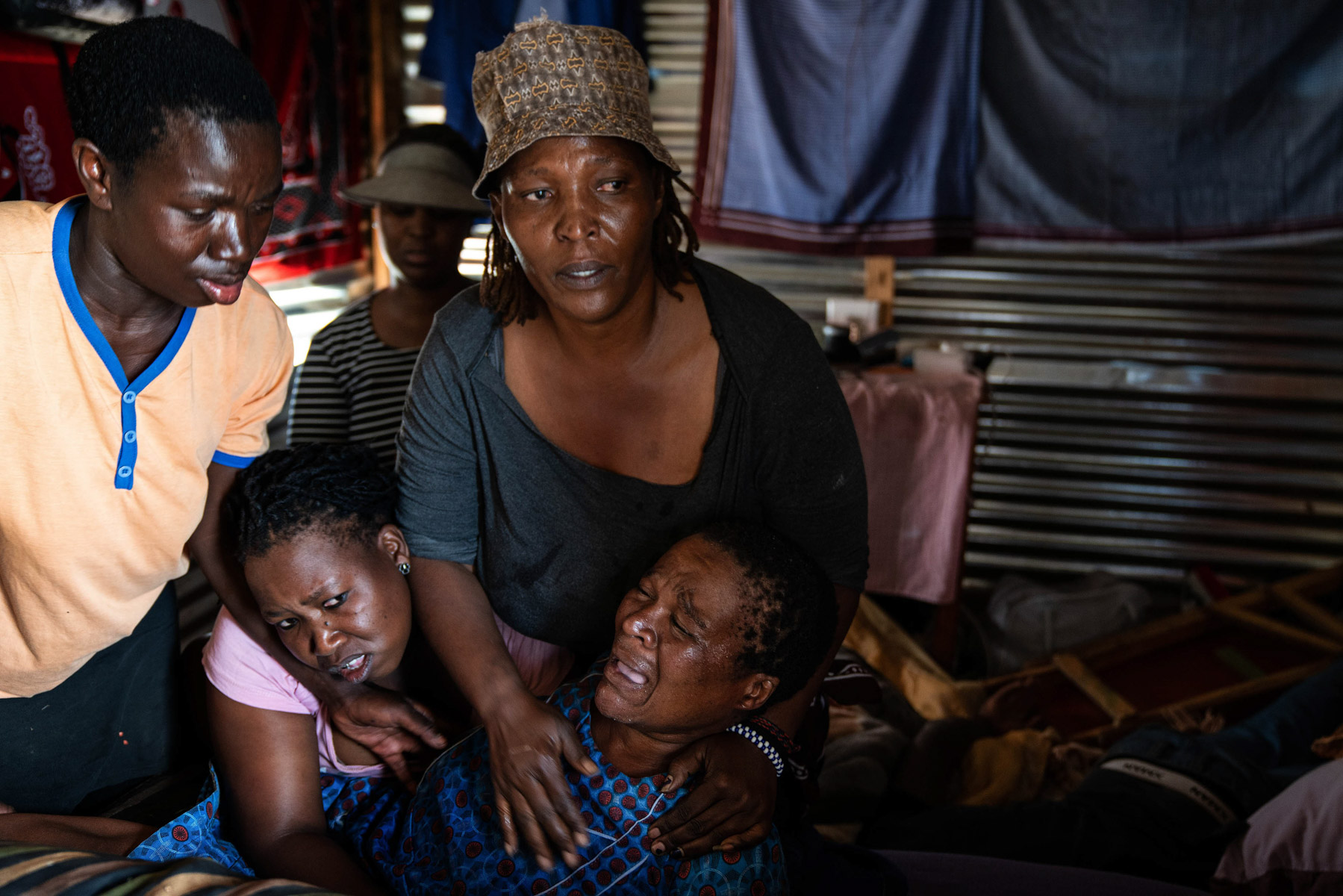 21 April 2020: Lindiwe Ndlovu helps Victoria Maphalale moments before she has a seizure. Police, who stormed the shack and fired rubber bullets, refused to take Maphalale to a clinic to receive medical attention. (Photograph by James Oatway)