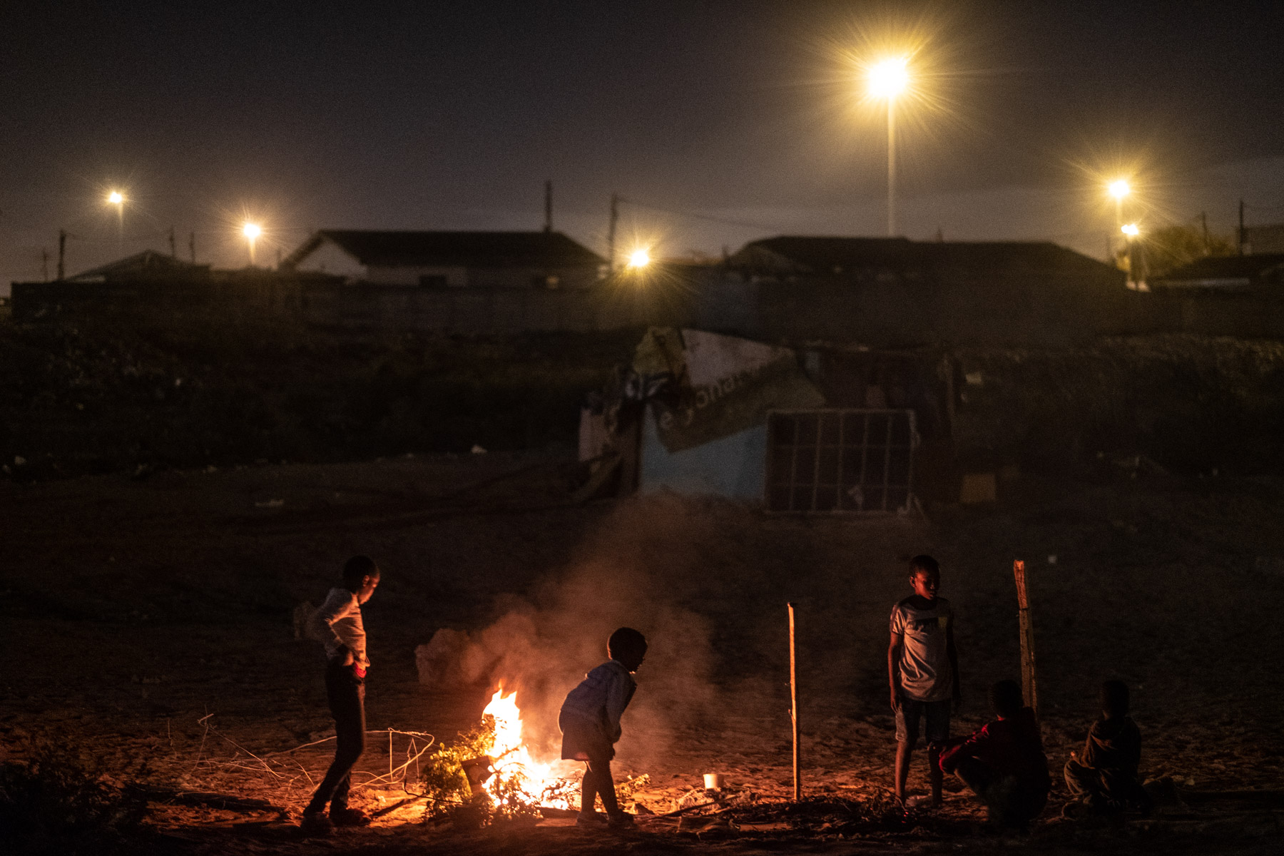 16 April 2020: Children who had been living in the demolished shacks play around a fire at night.