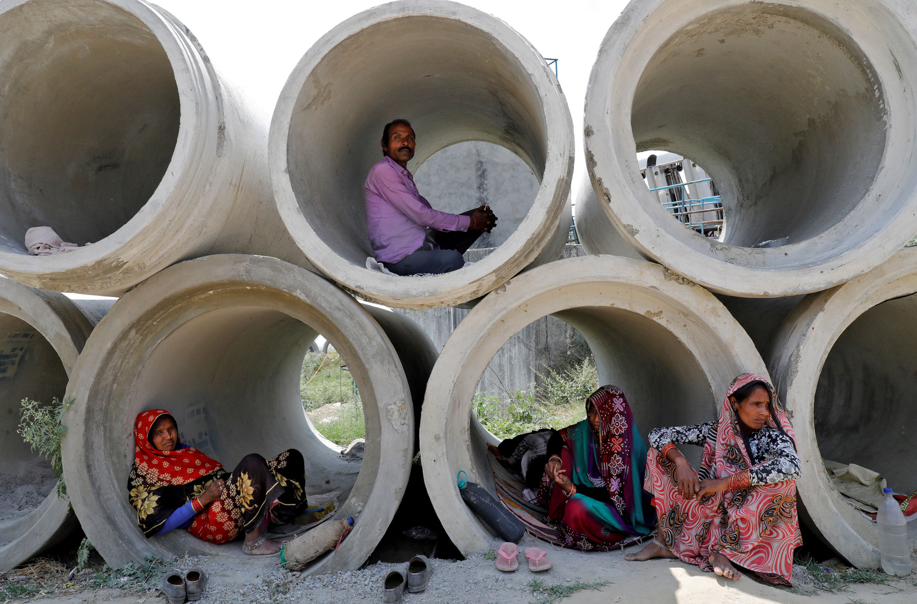 22 April 2020: Migrant labourers rest in cement pipes in Lucknow, India, during the country's nationwide lockdown. Many of them were stuck without food or shelter after it was imposed. (Photograph by Reuters/ Pawan Kumar)