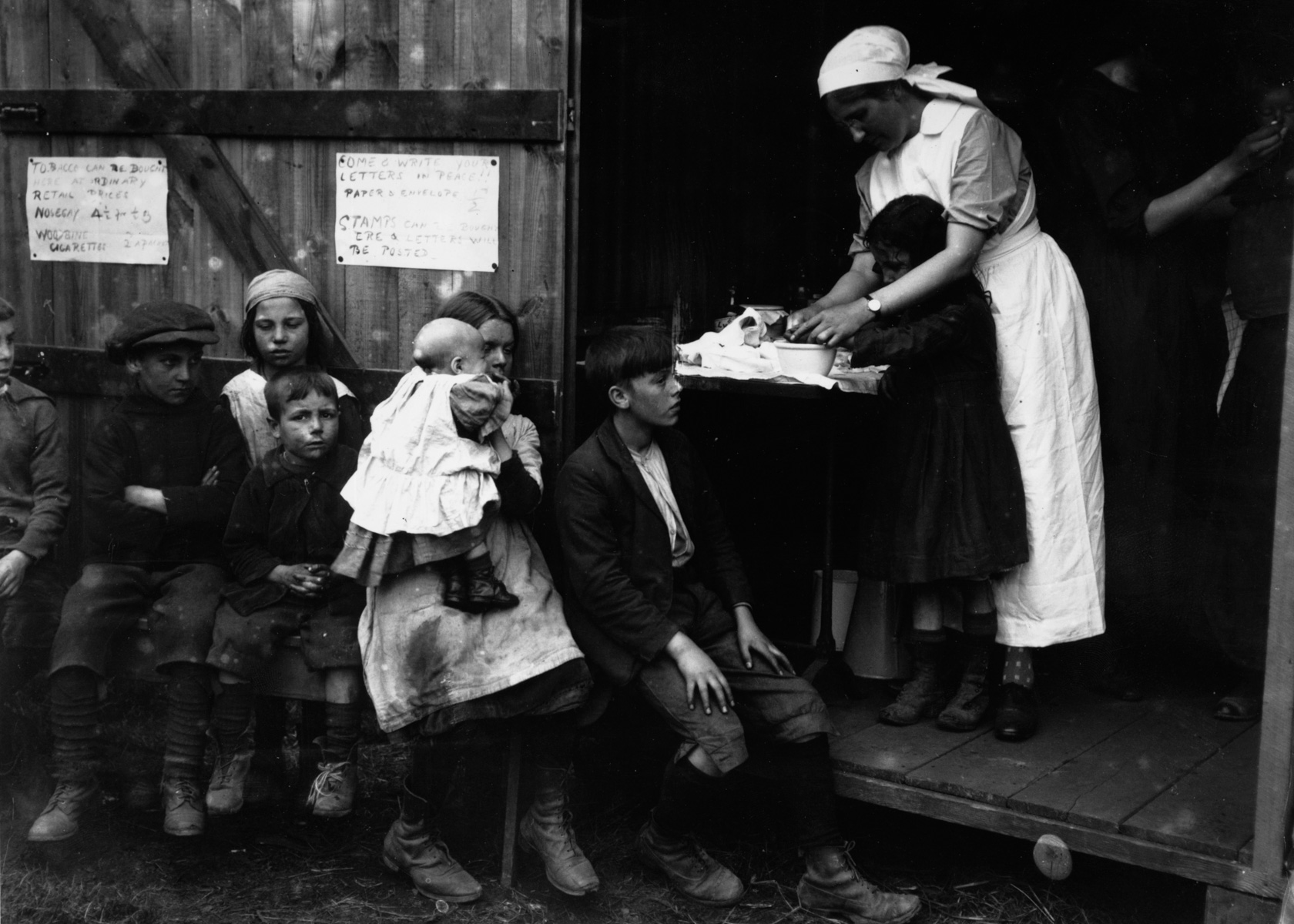 1920: A nurse treats a young boy at a first aid hut for hop pickers at Paddock Wood, Kent.  (Photograph by Central Press/ Getty Images)