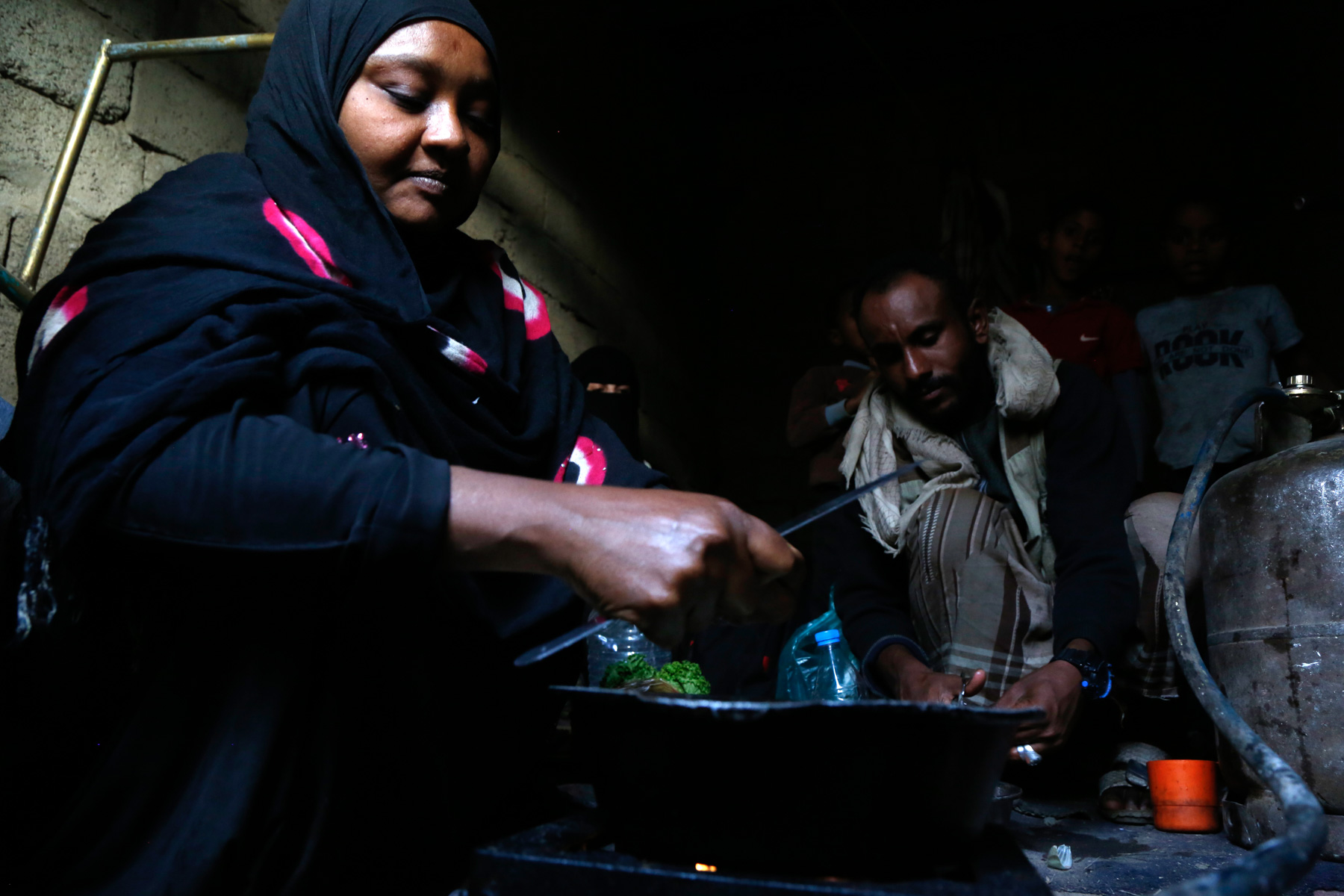 25 November 2019: Salwa Rajeh, a 45-year-old widow with four children, cooks in her rented shelter in Sana'a, Yemen. Intensifying fighting and airstrikes displaced her from Hodeida province three years earlier. 'Most days we sleep hungry.' (Photograph by Mohammed Hamoud/ Getty Images)