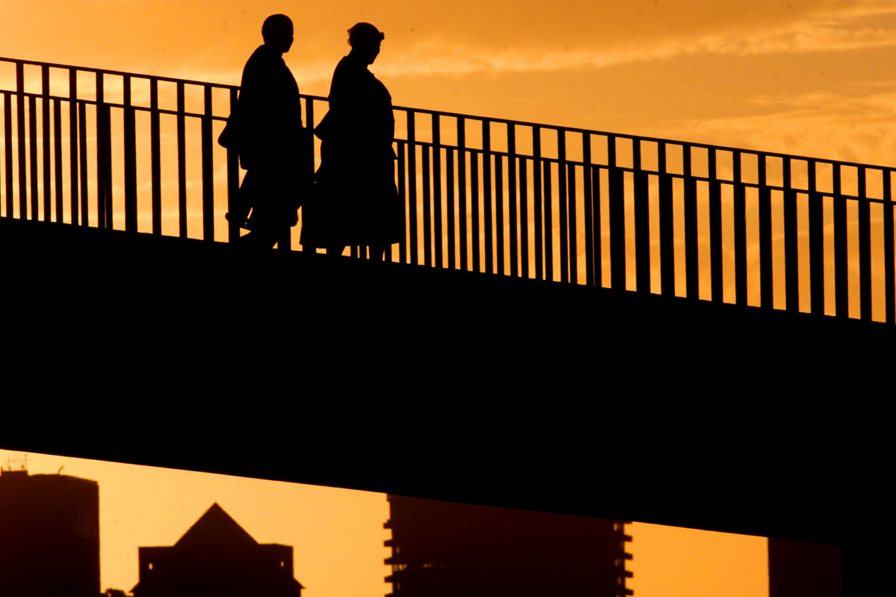 July 2002: Two domestic workers cross a bridge in Cape Town, backlit by the sun setting over the city as they return home. (Photograph by Reuters/ Mike Hutchings)