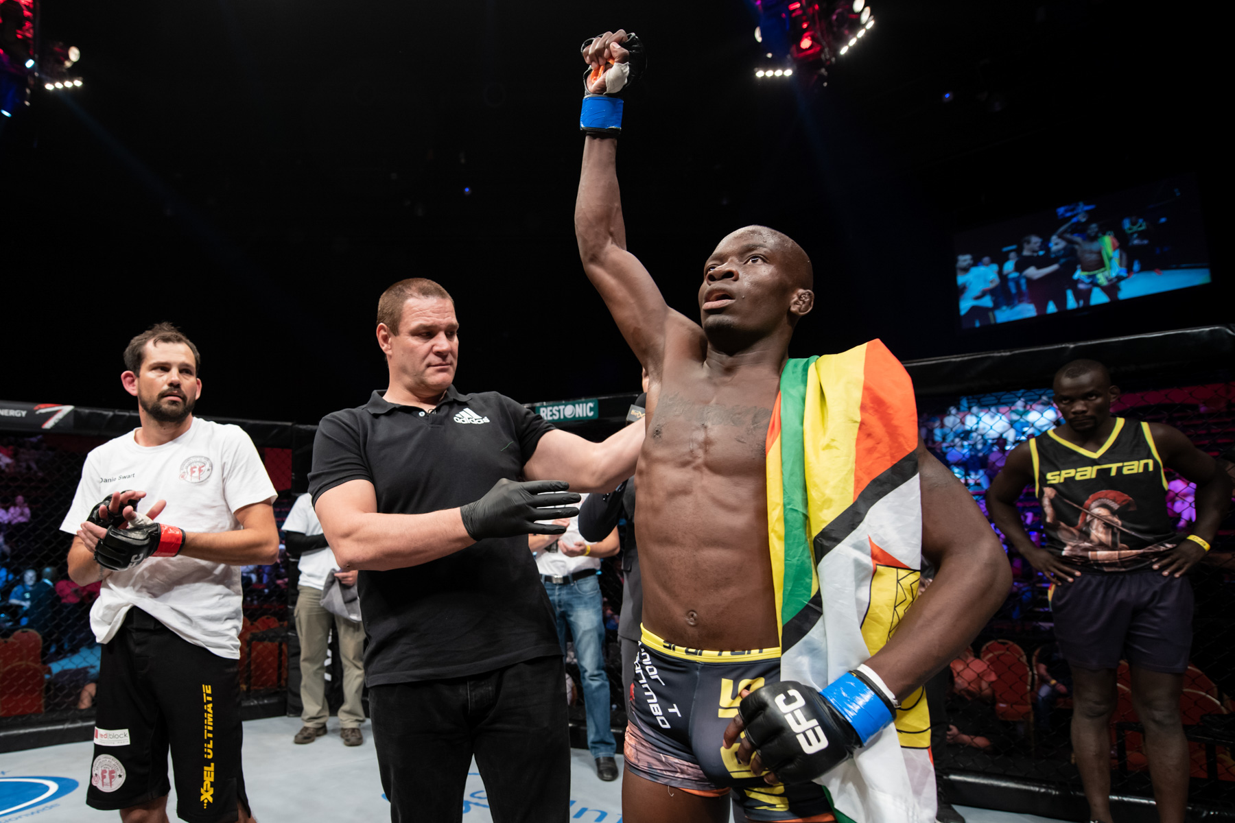 6 October 2018: Far right, Themba Gorimbo looks on as his brother Takunda Gorimbo celebrates defeating Danie Swart in the Fight Night for EFC 74 matchup at Carnival City in Johannesburg. (Photograph by Anton Geyser/ EFC Worldwide/ Gallo Images)