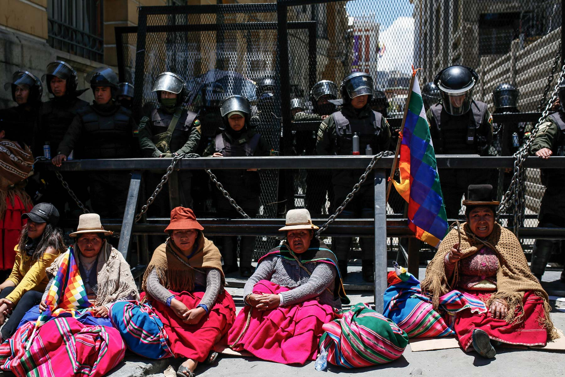 18 November 2019: Indigenous women sit next to a police barricade during a demonstration supporting former President Evo Morales and opposing incumbent President Jeanine Añez in La Paz, Bolivia. (Photograph by Gaston Brito Miserocchi/ Getty Images)