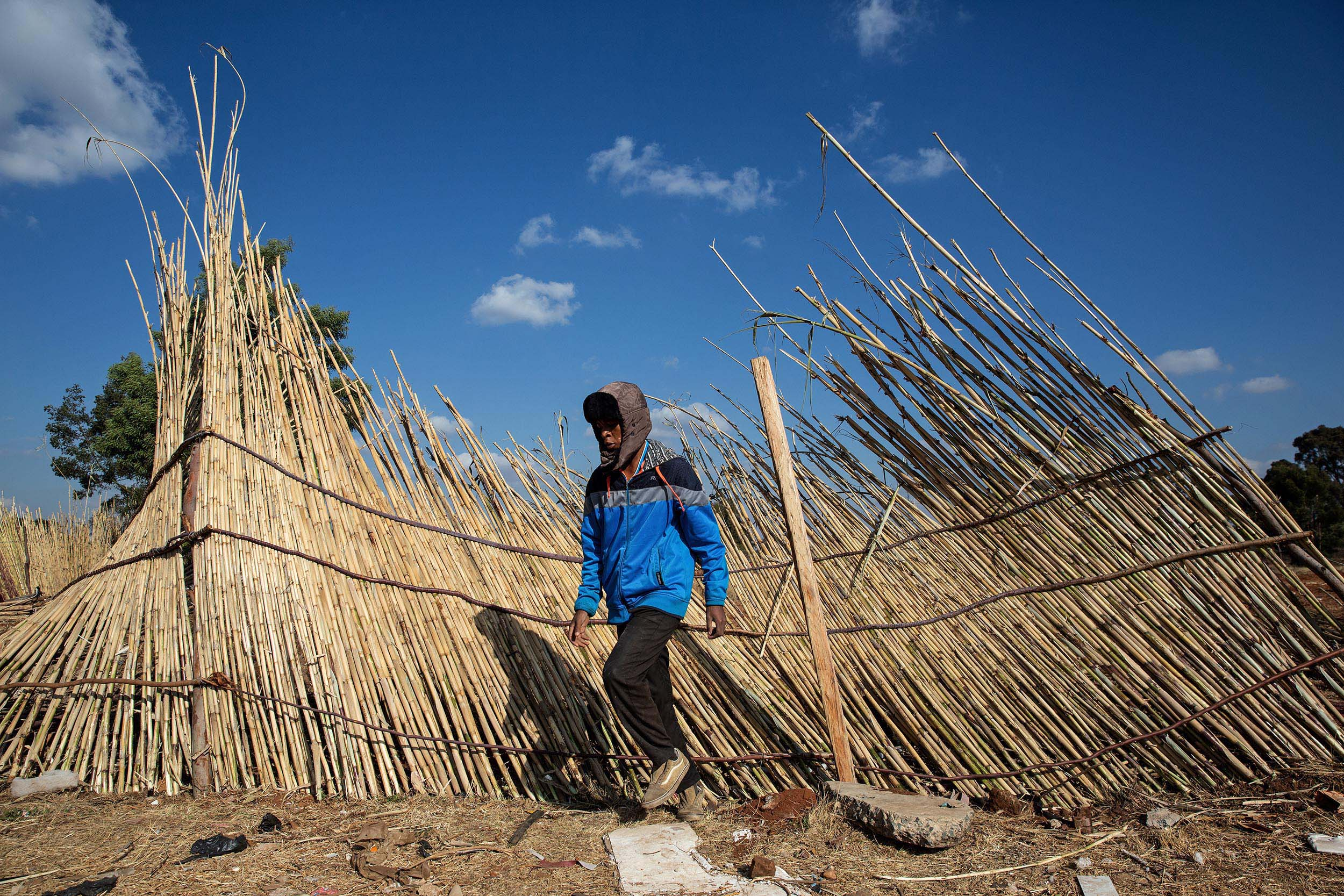 9 July 2020: A man fixes a fence blown down by the wind. The fence encloses a field that has been set aside to grow vegetables to assist the hungry Makause community.