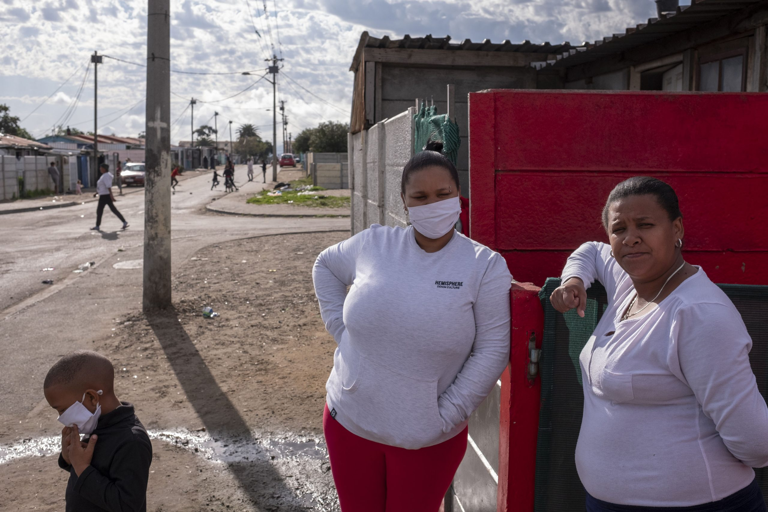 9 June 2020: From left, Angelique Nico, a former colleague of Petrus Miggels, with her son and Nora Southgate, Cecilia Meintjies' niece, stand outside the couple's house in Uitsig.
